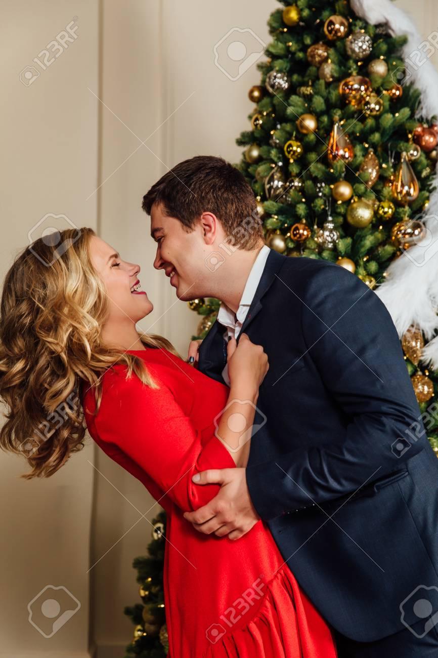 porträt eines schönen paares auf einem weihnachtsbaumhintergrund. neues  jahr, rotes kleid, blauer anzug.