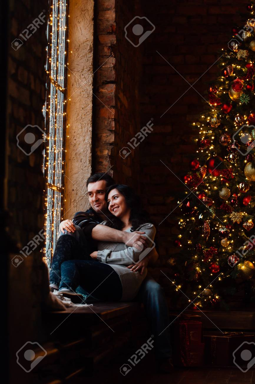 The Christmas Loft.Couple Of Lovers Hugs Sitting On The Windowsill In The Christmas