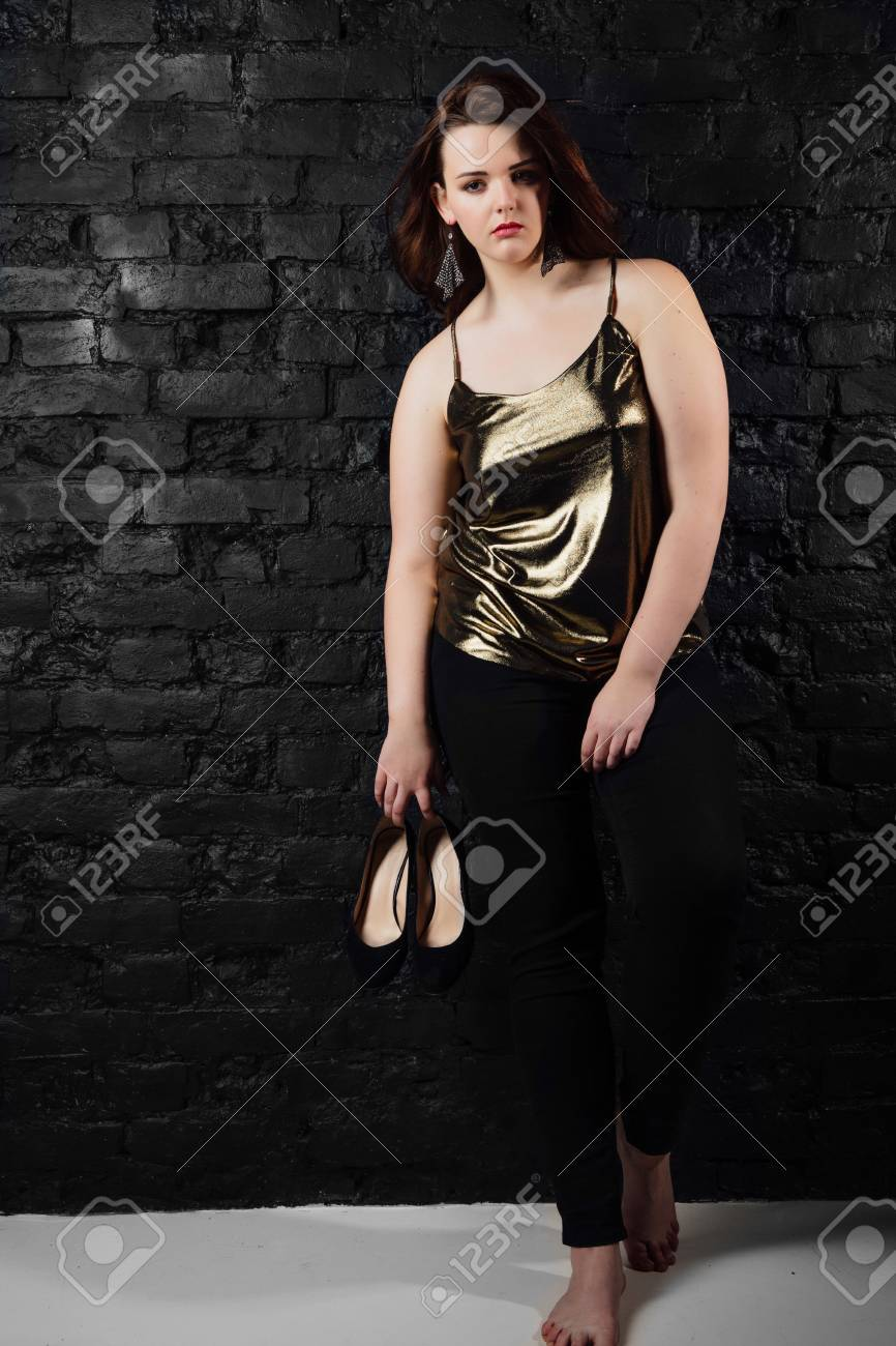 800d278fbfdf0 plus size model in a gold blouse and black jeans on a brick loft background.