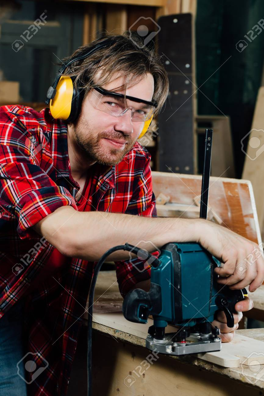 Carpenter working of manual hand milling machine in the carpentry workshop.  joiner. Stock Photo