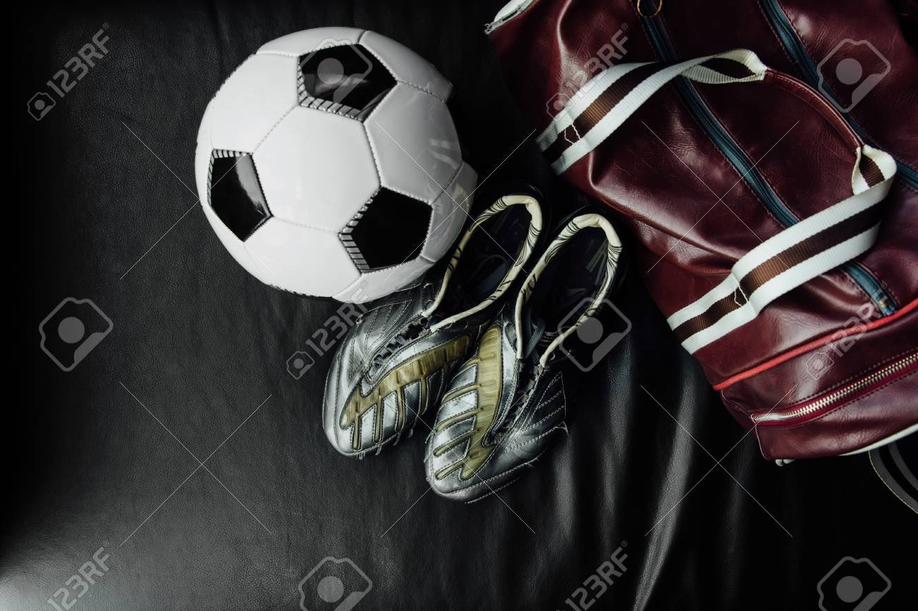Flat lay soccer football accessories on a dark leather background