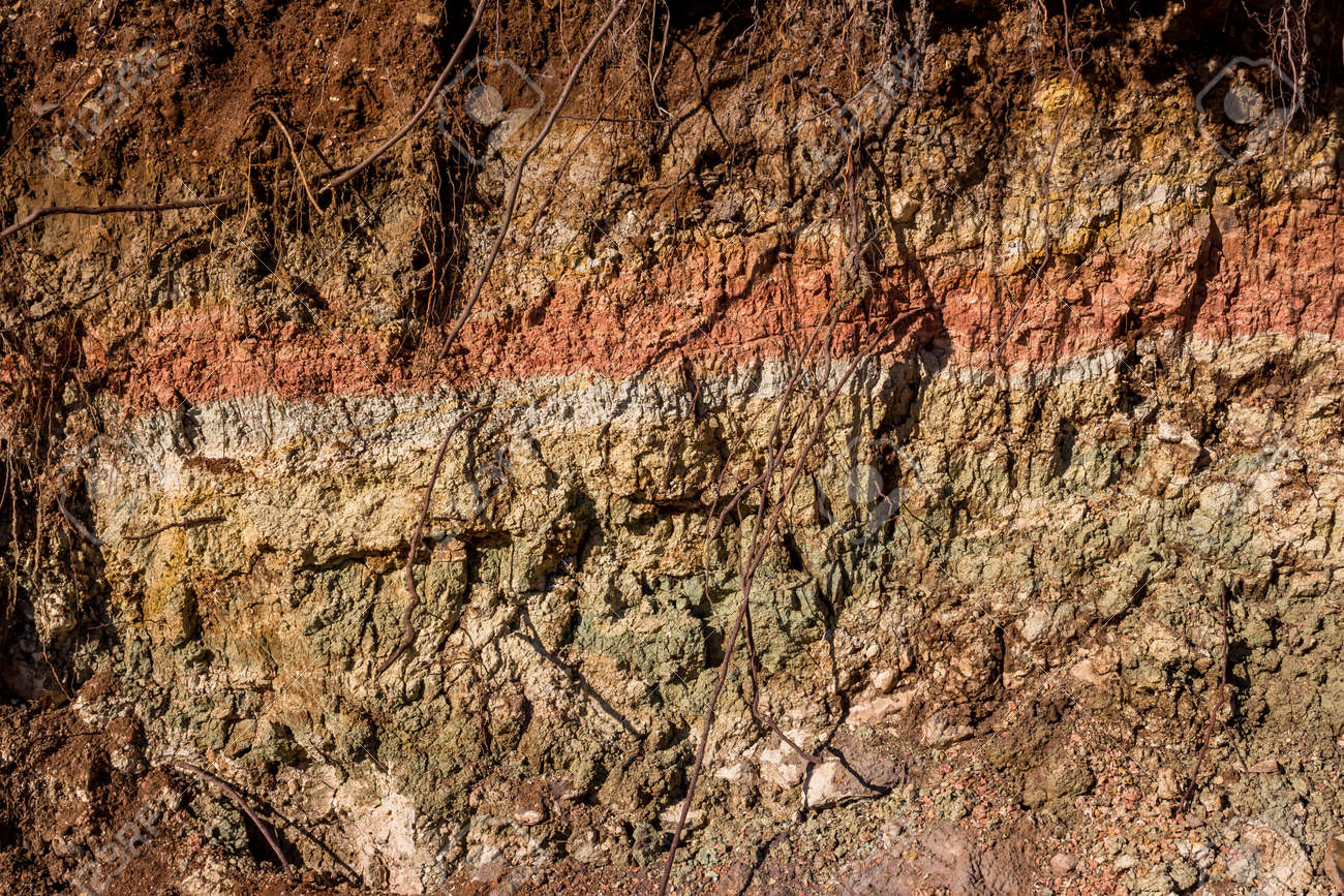 Clay layer folded in layers of different colors dried in the sun - 169566643