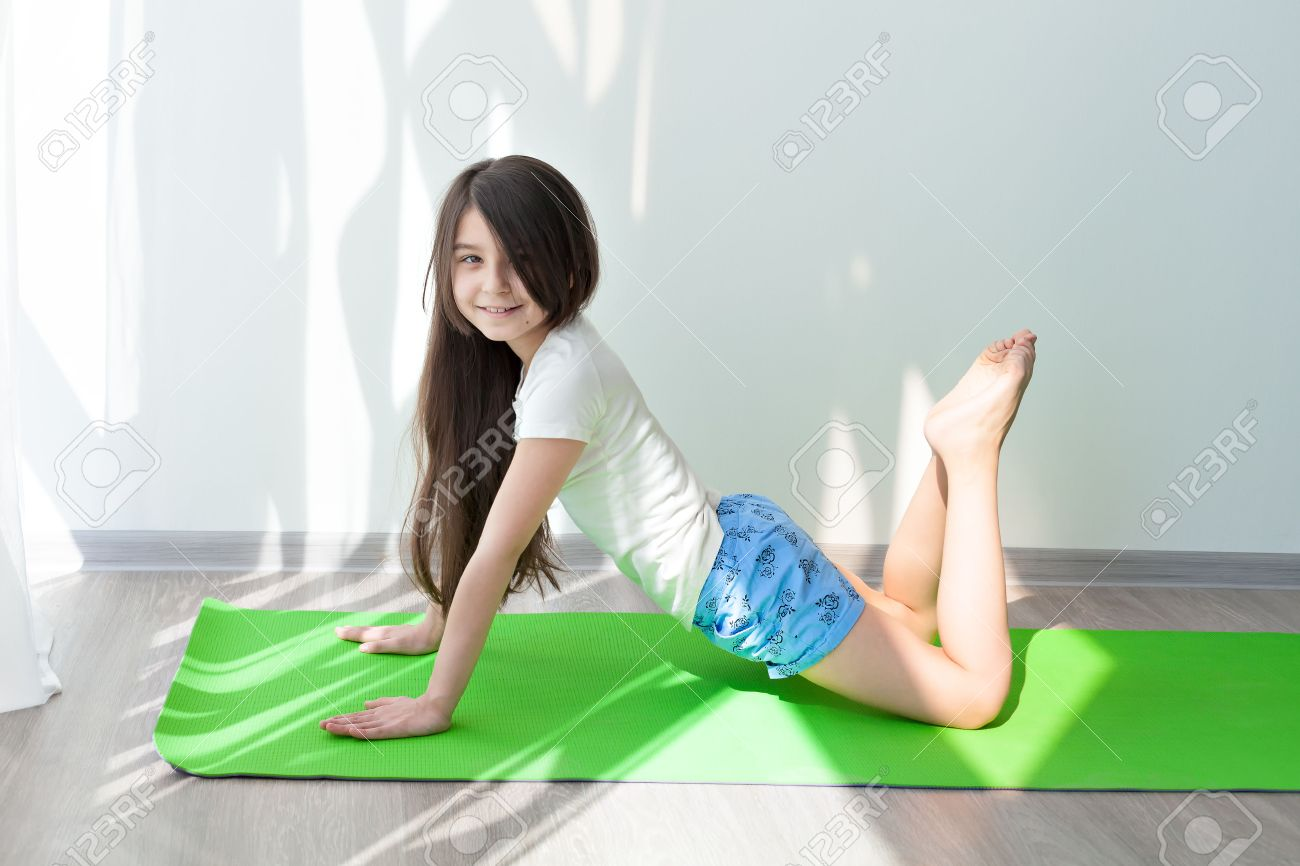 Little Girl Doing Gymnastics On A Green Yoga Mat. Children's.. Stock Photo,  Picture And Royalty Free Image. Image 55893432.