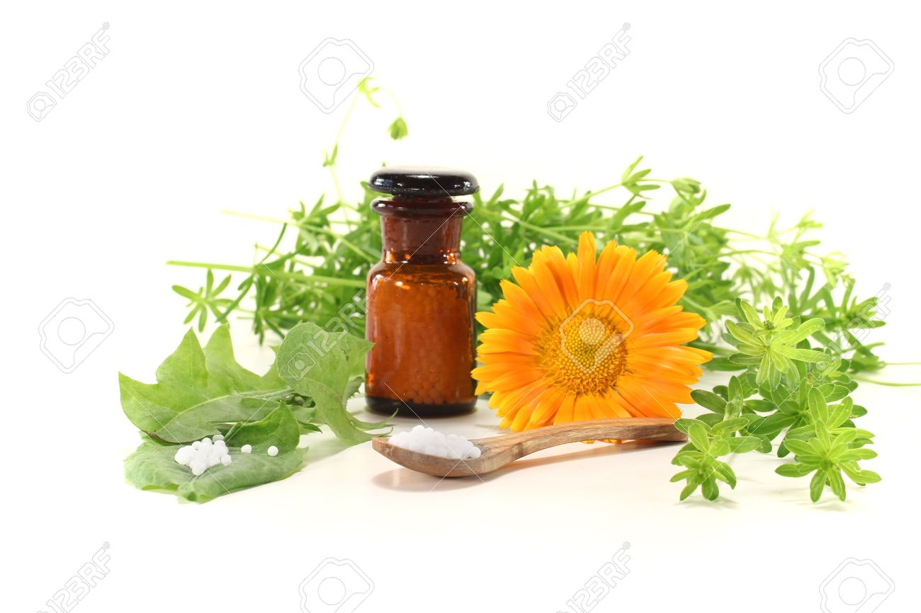 Homeopathy with globules, an apothecary jar, natural herbs and marigolds Stock Photo - 13625922