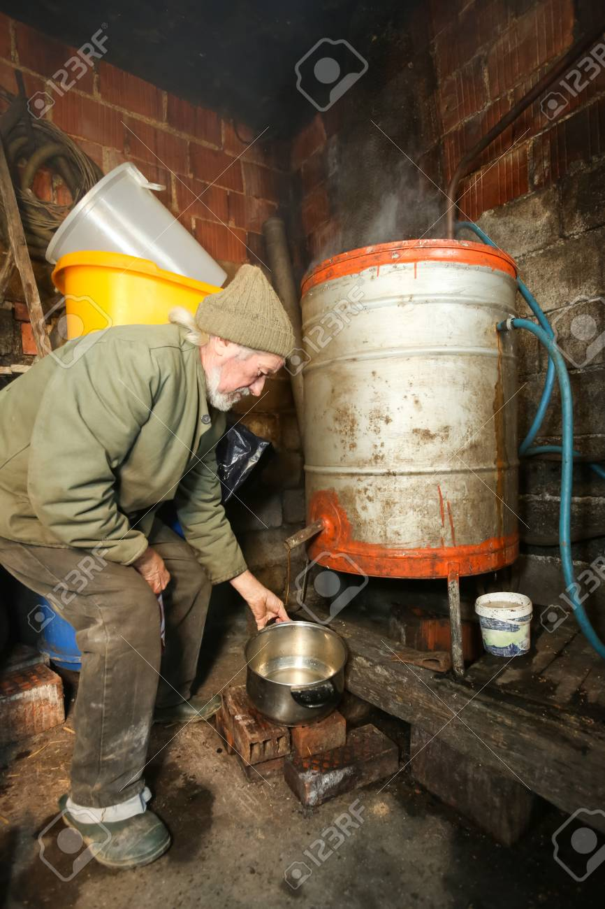 An older man making homemade brandy in the boiler in his shed. Stock Photo -