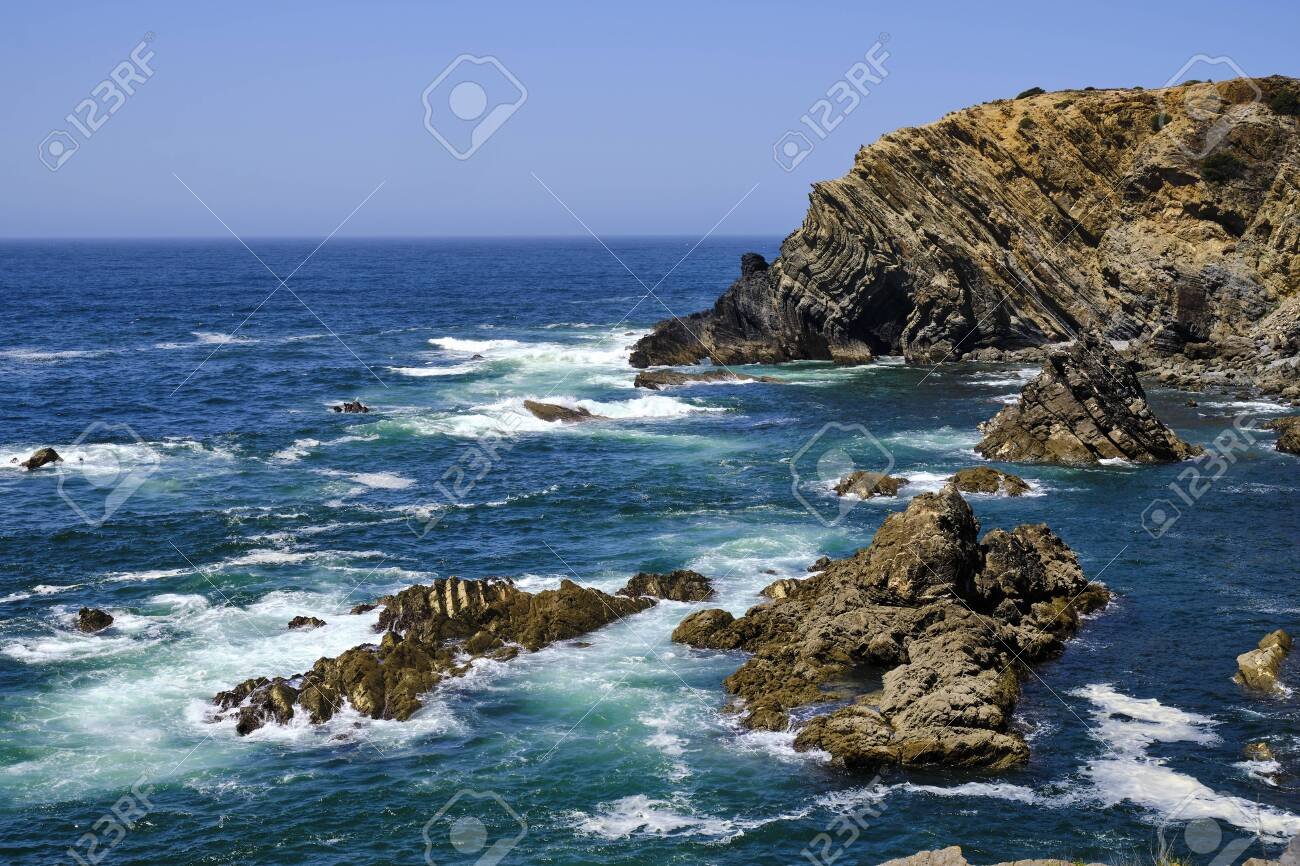 Waves crash on the cliff. Solo Backpacker Trekking on the Rota Vicentina and Fishermen's Trail in Alentejo, Portugal. Walking between cliff, ocean, nature and beach. - 145734469