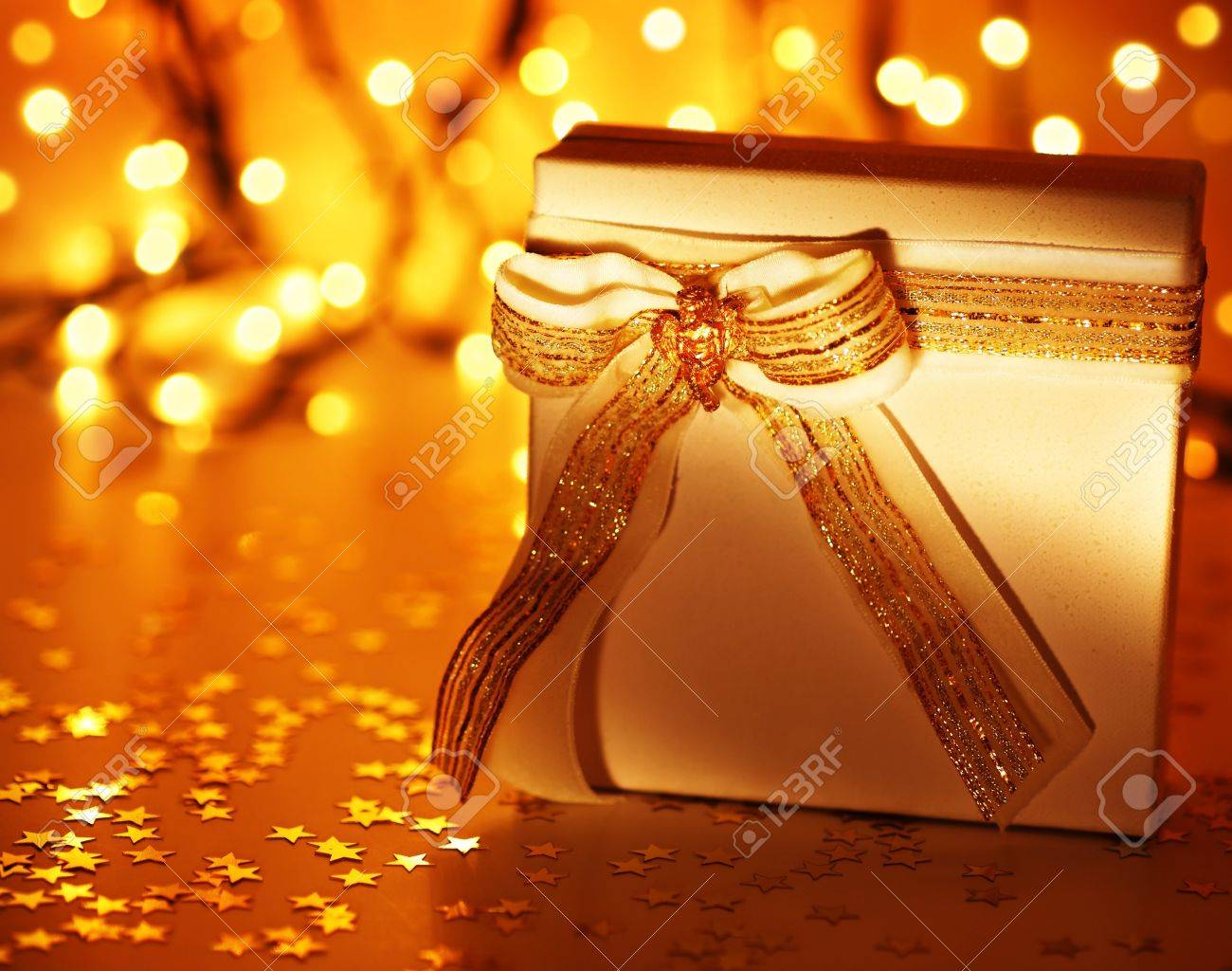 Gold holiday background with white present gift box, Christmas ornament and new year decoration over defocused lights Stock Photo - 8184108