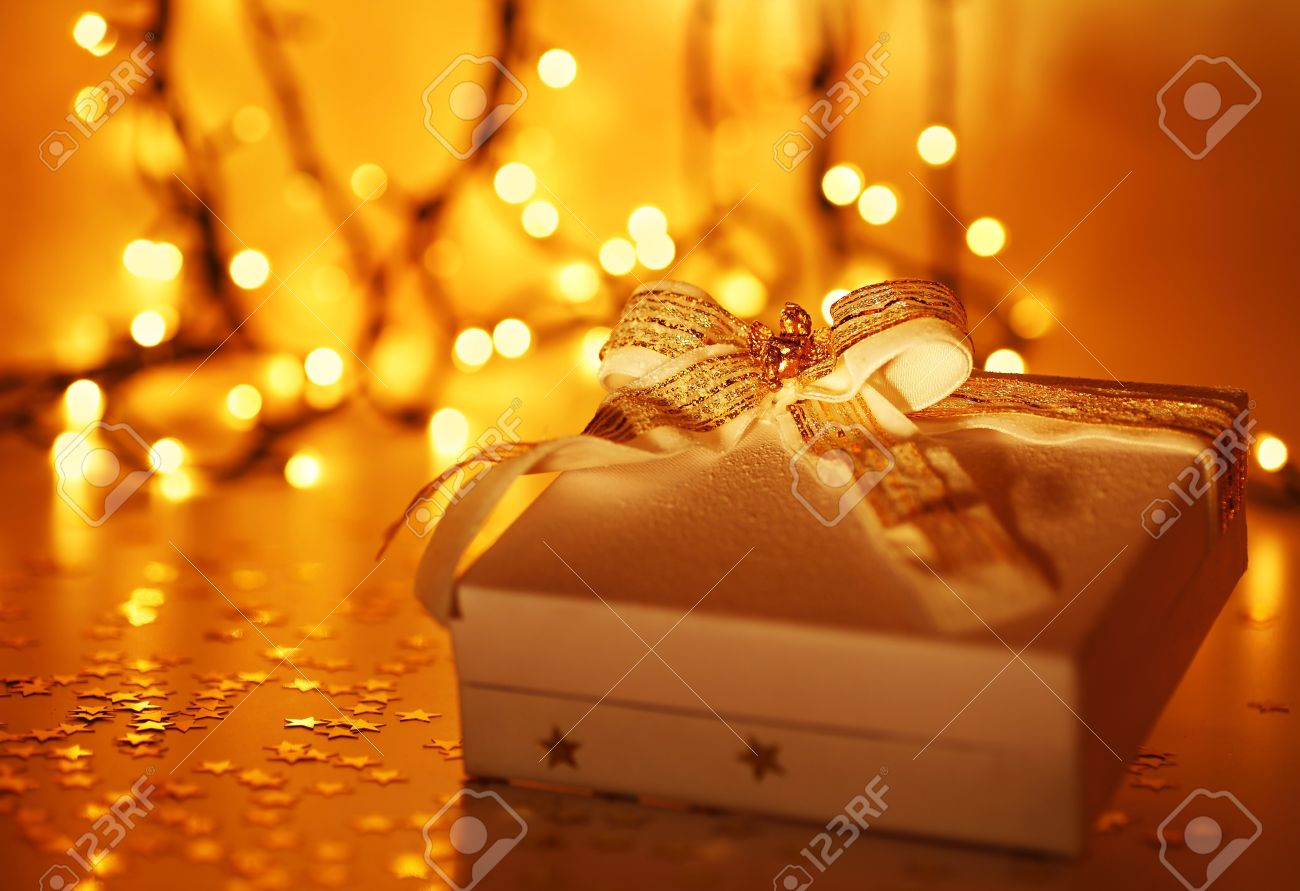 Gold holiday background with white present gift box, Christmas ornament and new year decoration over defocused lights - 8323874