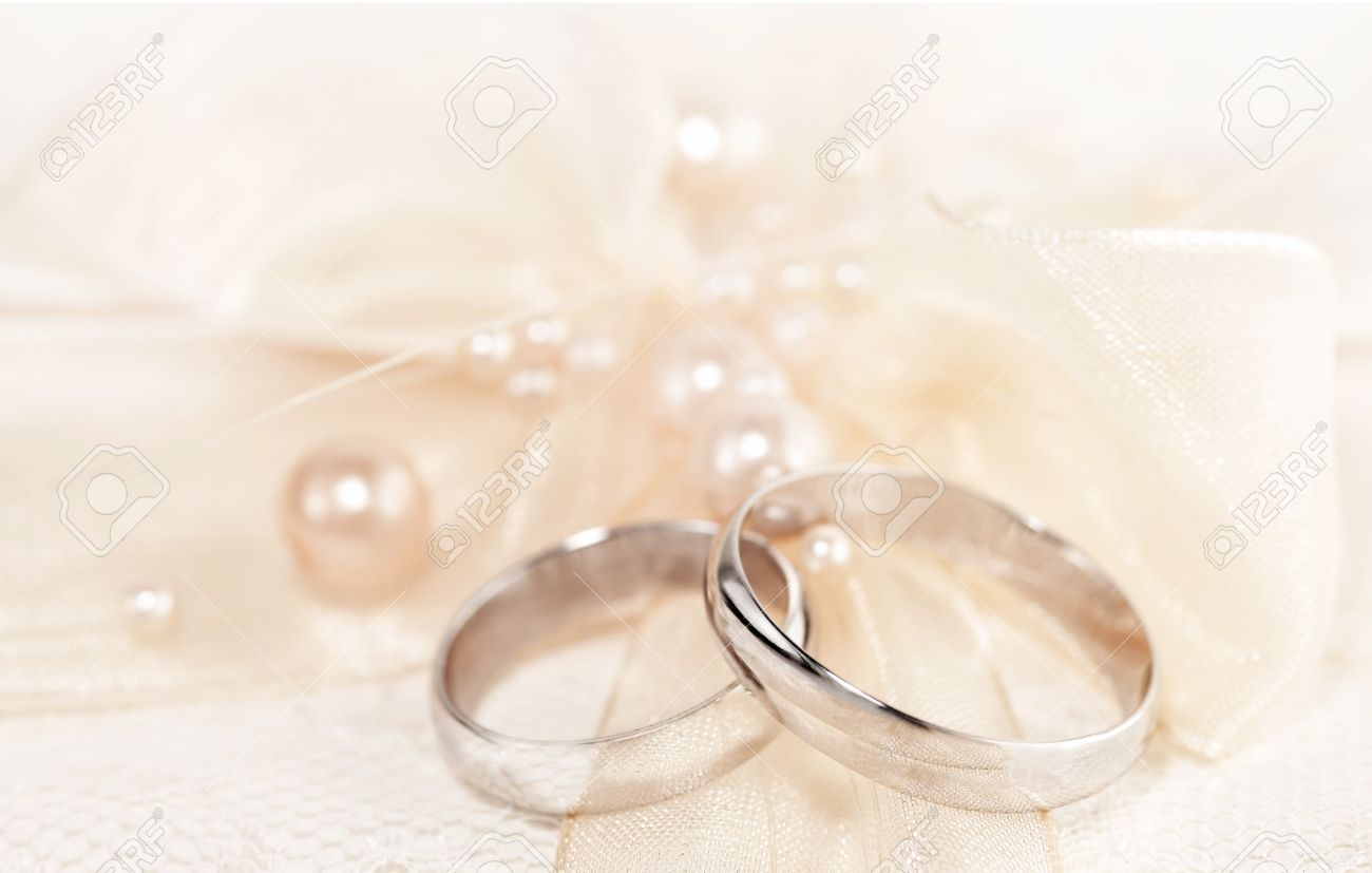 Pair Of Golden Wedding Rings Over Invitation Card Decorated With Silk Bow &  Pearls Stock Photo