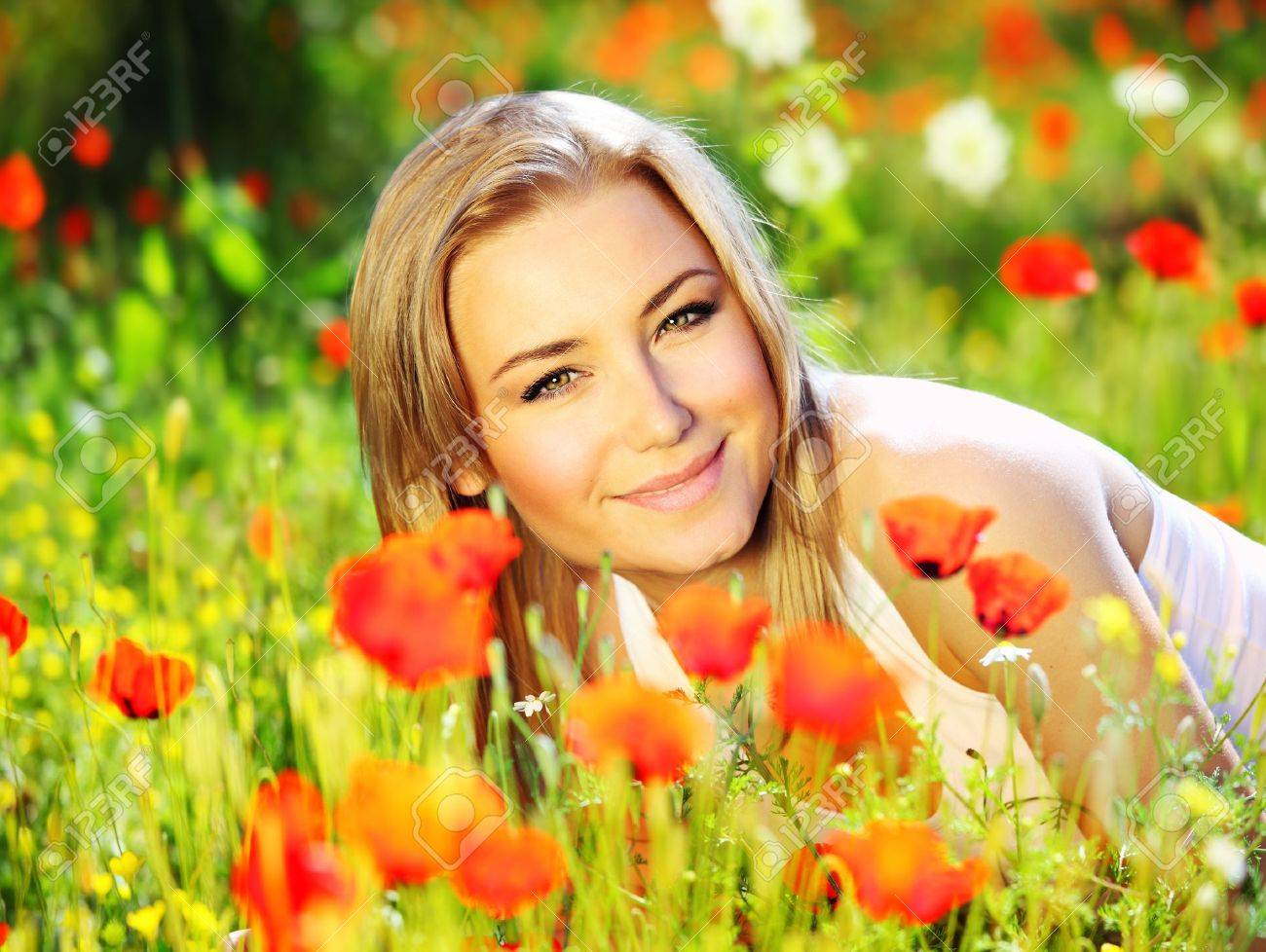 Young beautiful girl laying on the poppy flowers field, outdoor portrait, summer fun concept Stock Photo - 9642293