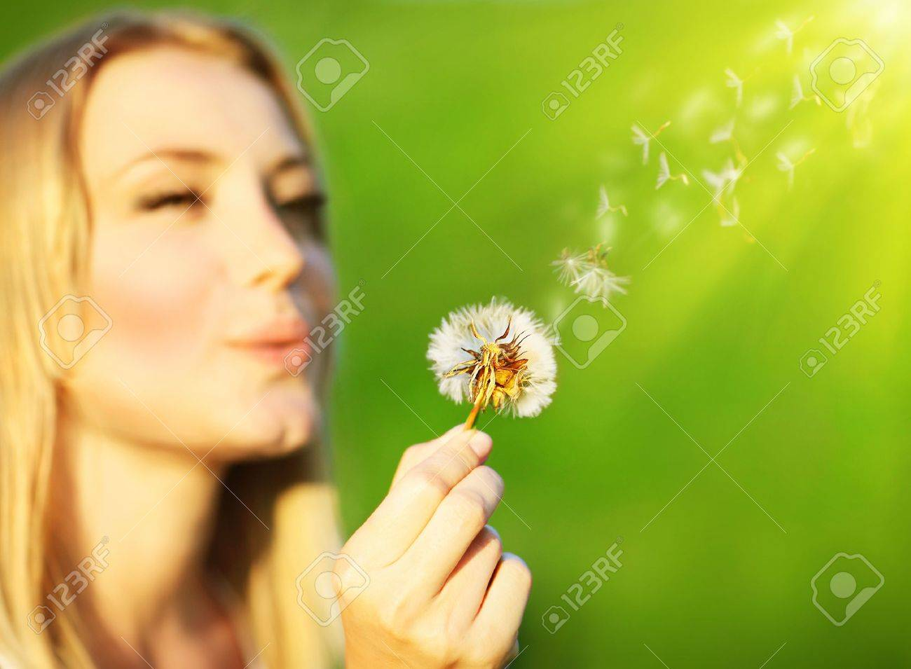 Happy beautiful girl blowing dandelion, over green nature background, selective focus, wish concept Stock Photo - 9642286