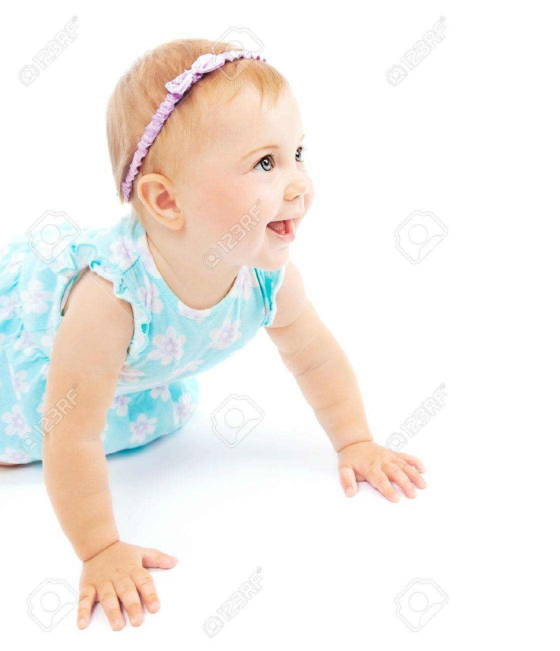 Adorable little baby girl laughing, crawling and playing at studio, isolated on white background Stock Photo - 9996945