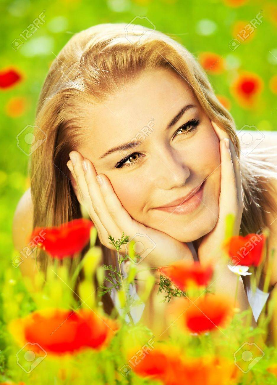 Lovely happy female closeup portrait, lying down in the poppy flower field, enjoying nature, summertime leisure concept Stock Photo - 10082406