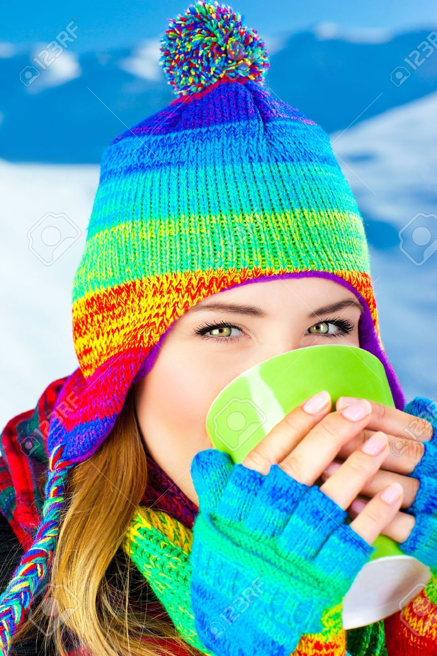 beautiful girl drinking hot chocolate outdoor in winter, happy