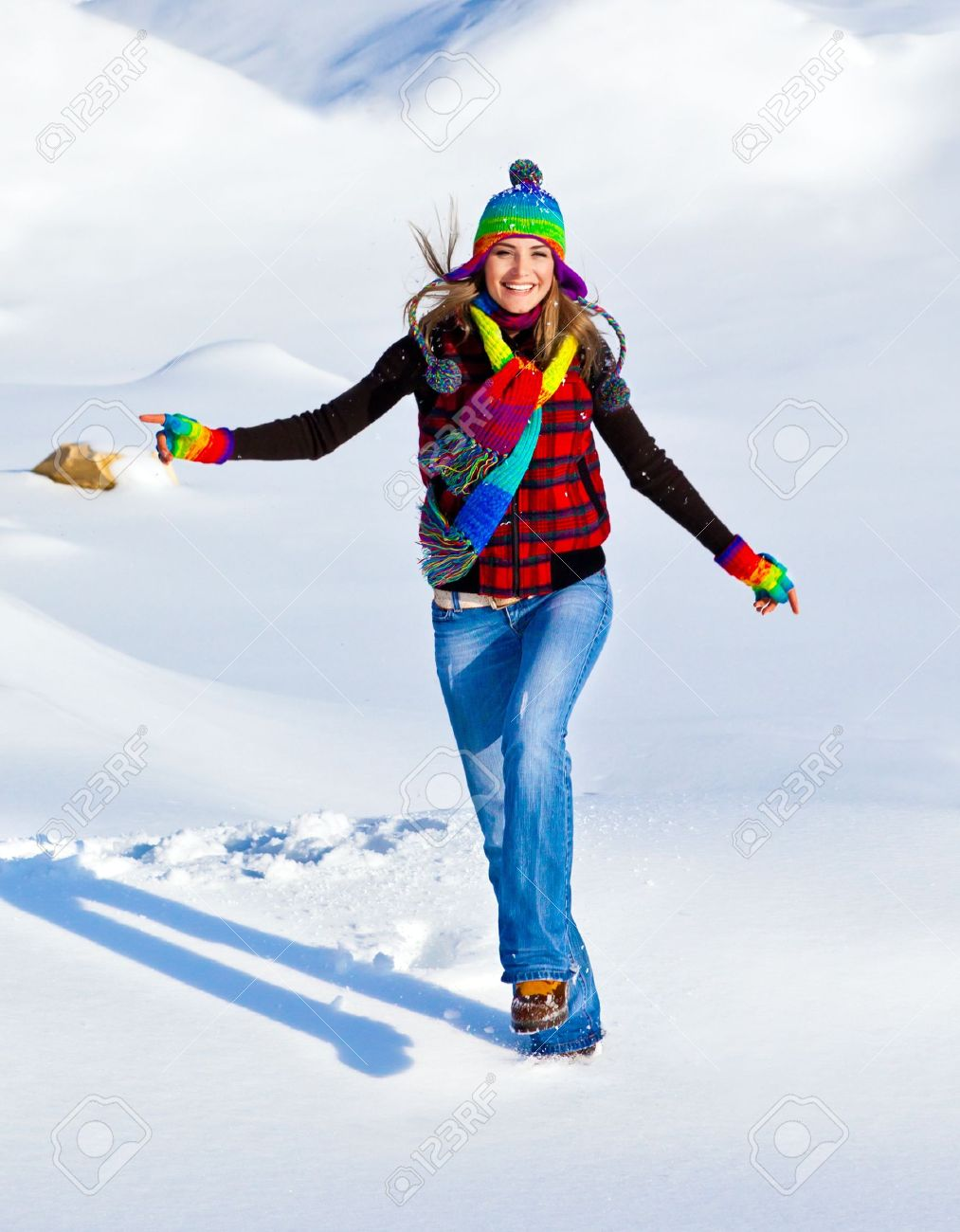 Happy girl running in the snow, teen outdoor winter activities, female having fun at Christmastime, woman wearing colorful clothes, freedom and nature joy concept Stock Photo - 11599872