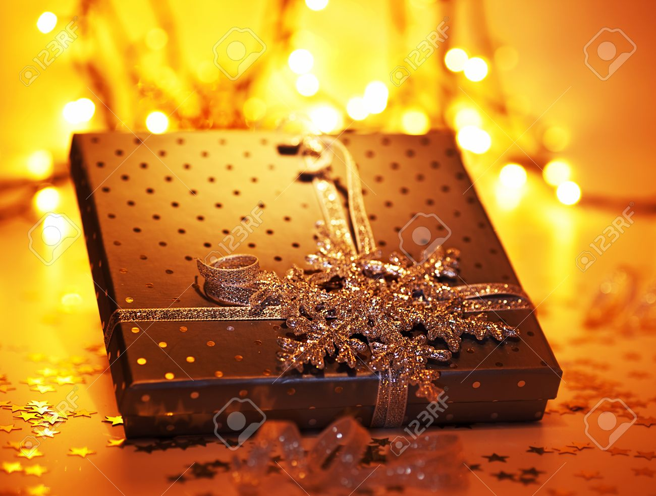 Golden gift box, Christmas ornament and winter holidays decoration over blur bokeh tree lights, festive pesent with snowflake, warm yellow glowing background Stock Photo - 11600325