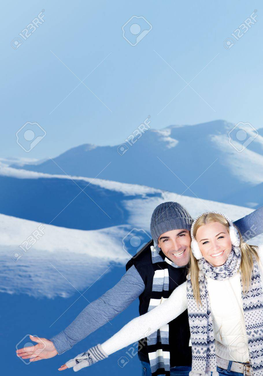 Happy couple having fun, raised arms flying hands, outdoors at winter snowy mountains, people at nature, blue wintertime landscape background, Christmas vacation holidays, love concept Stock Photo - 12065352