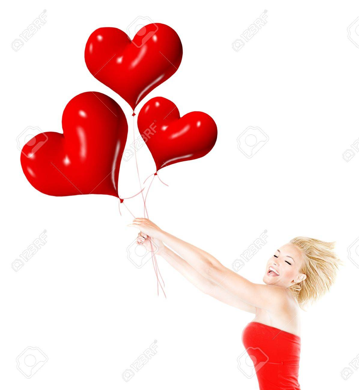 Happy girl flying, female holding red heart balloons, woman having fun and laughing, body isolated on white background, crazy in love concept Stock Photo - 12065339