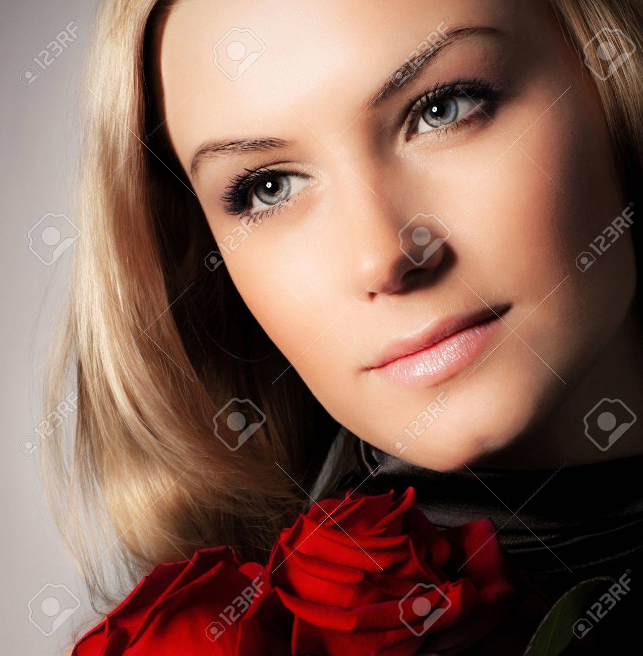 Stylish beautiful young woman holding red roses bouquet, tender flowers in hands, blond female over dark background, gorgeous girl with fresh plant, lady in love concept Stock Photo - 12589041