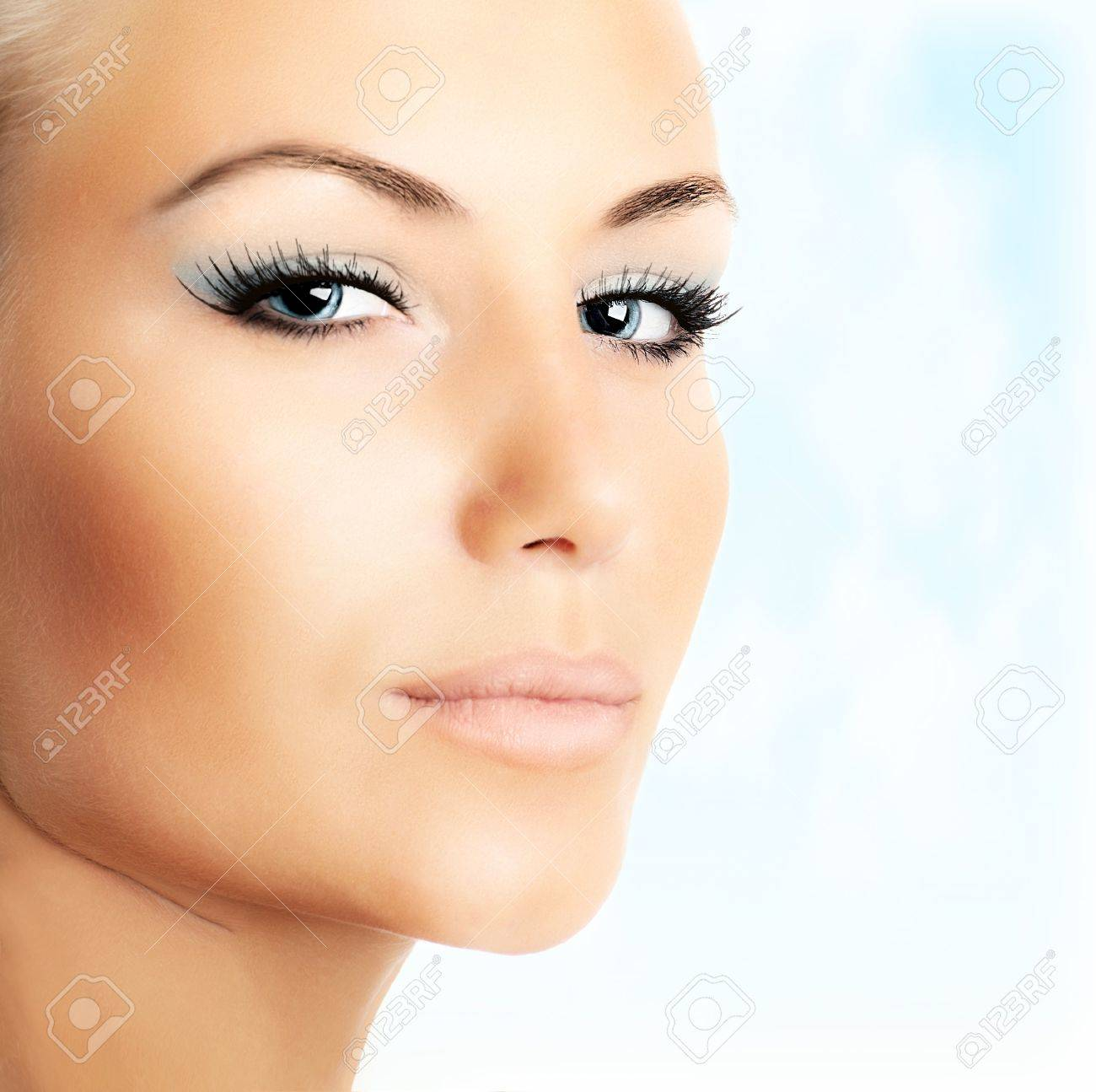 Closeup of beautiful female face over abstract blue sky background Stock Photo - 12879447