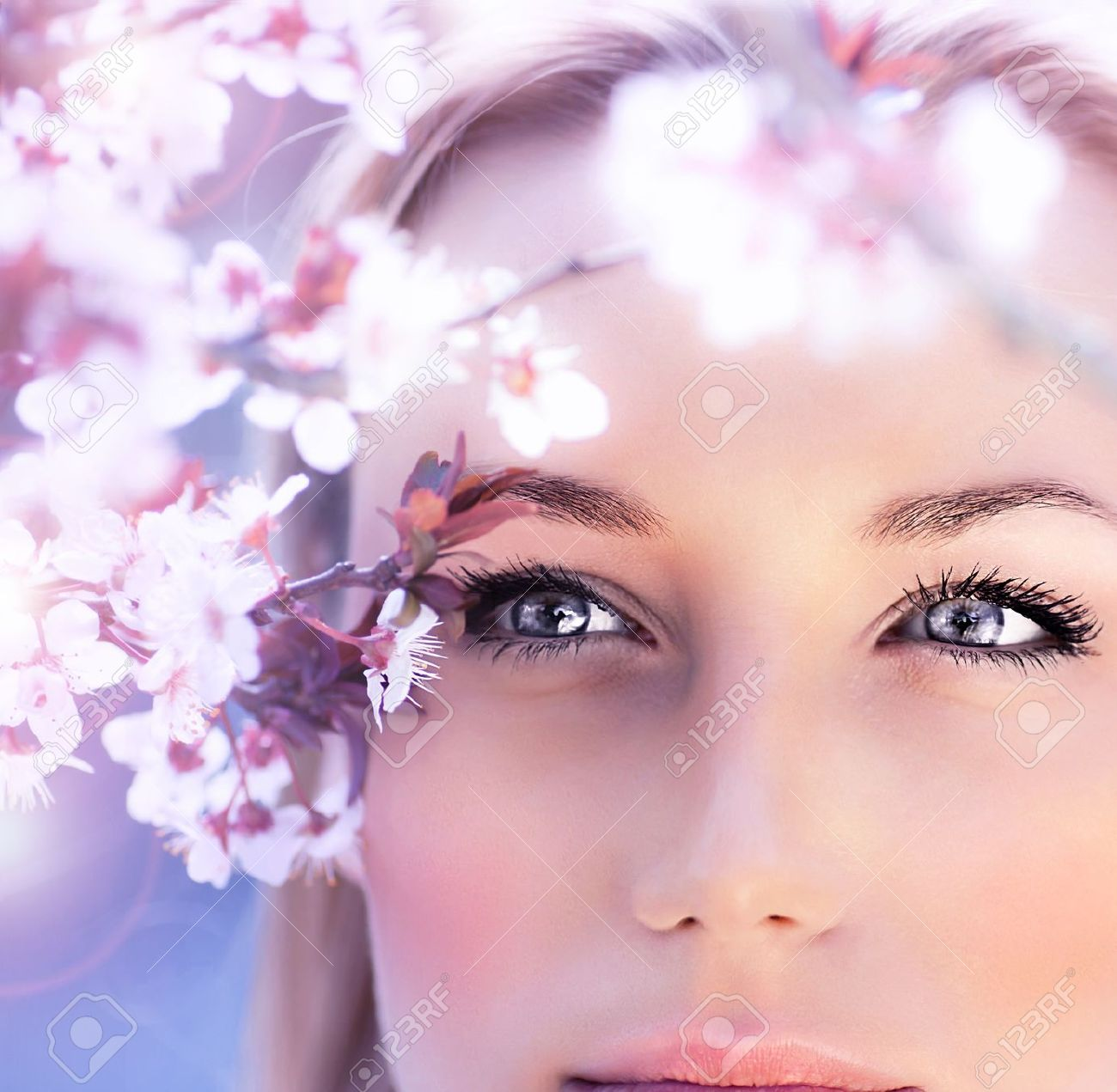 Sensual portrait of a spring woman, beautiful face, close up on blue eyes, female enjoying cherry blossom, dreamy girl with pink fresh flowers outdoor, seasonal nature, tree branch and natural beauty Stock Photo - 12879936