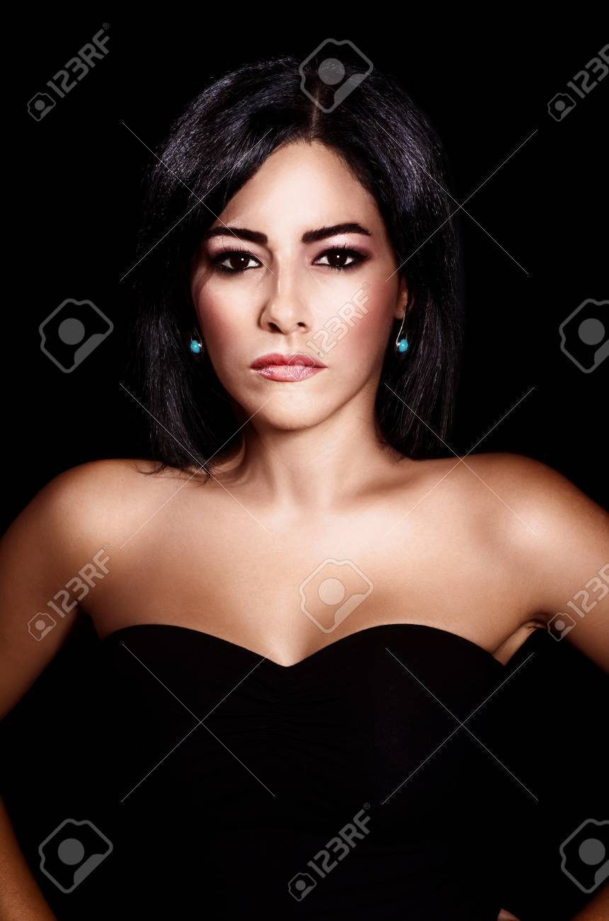 a sexy brunette woman isolated on black background, portrait of gorgeous arabian female, luxury young lady with stylish makeup, beautiful girl wearing fashionable black dress Stock Photo - 15238285