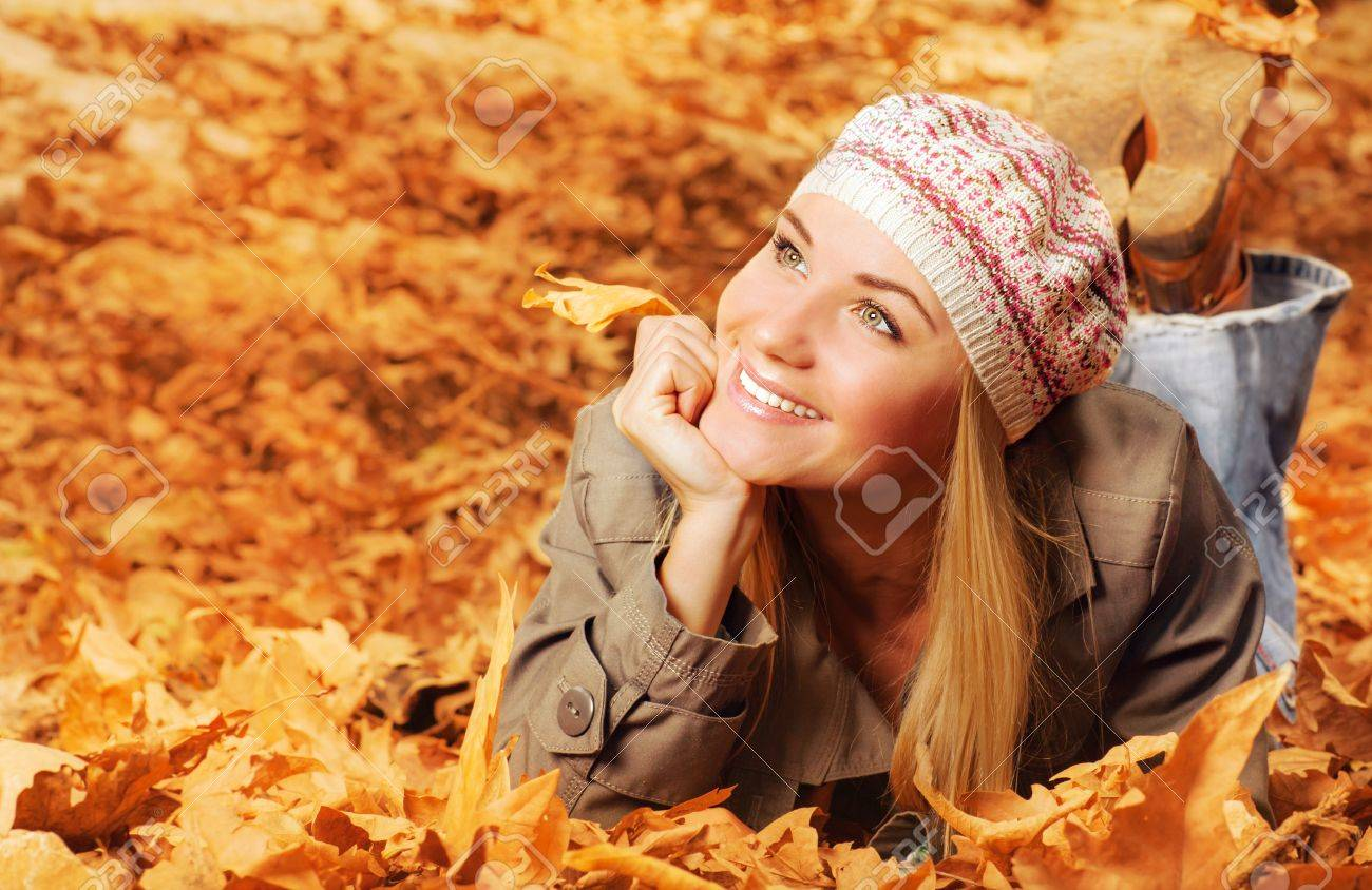 Image of cheerful teen laying down on the ground covered dry autumnal foliage in beautiful park Stock Photo - 16010612
