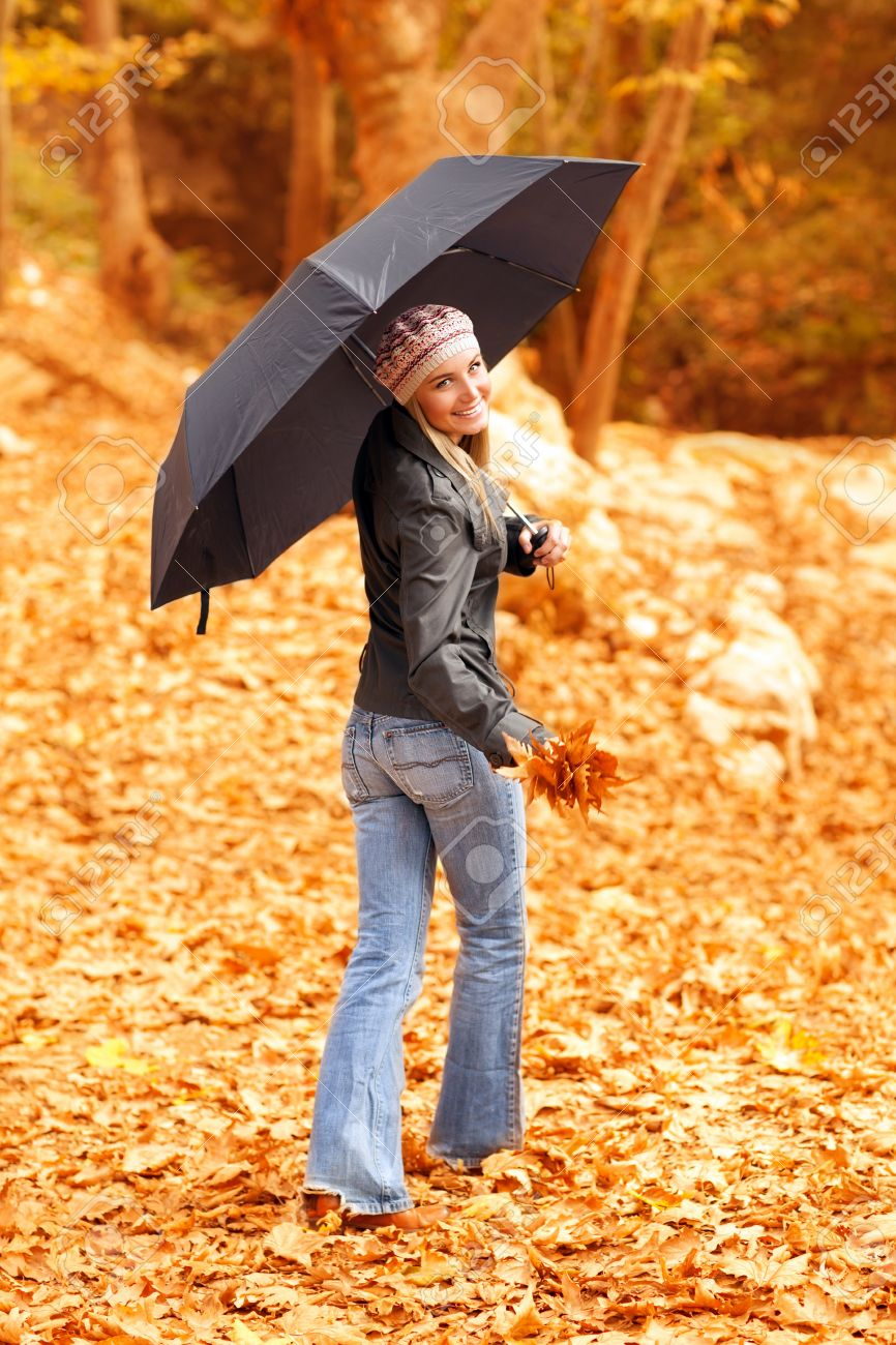 Image of attractive young lady standing under black umbrella in autumn forest in rainy weather, active healthy woman wearing colorful warm hat, nice blond girl holding dry autumnal leaves in hand Stock Photo - 16010525