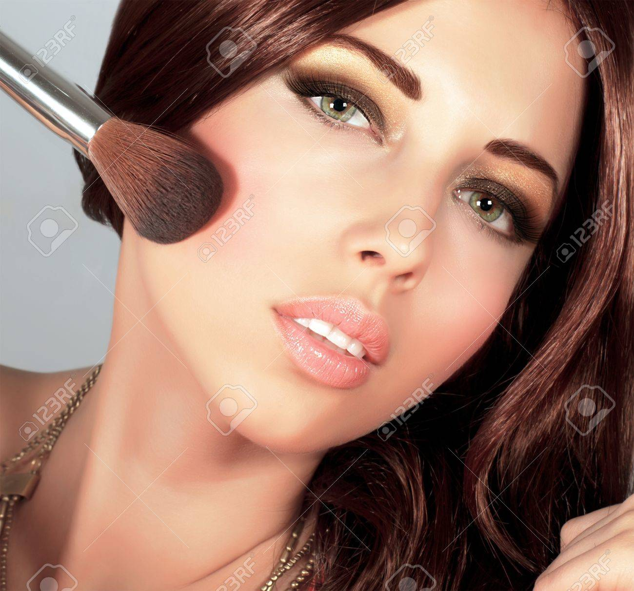 Photo of beautiful stylish woman doing makeup, closeup portrait of pretty female with silky brown hair holding brush for blush isolated on grey background, smoky eyes, fashionable makeover Stock Photo - 16367631