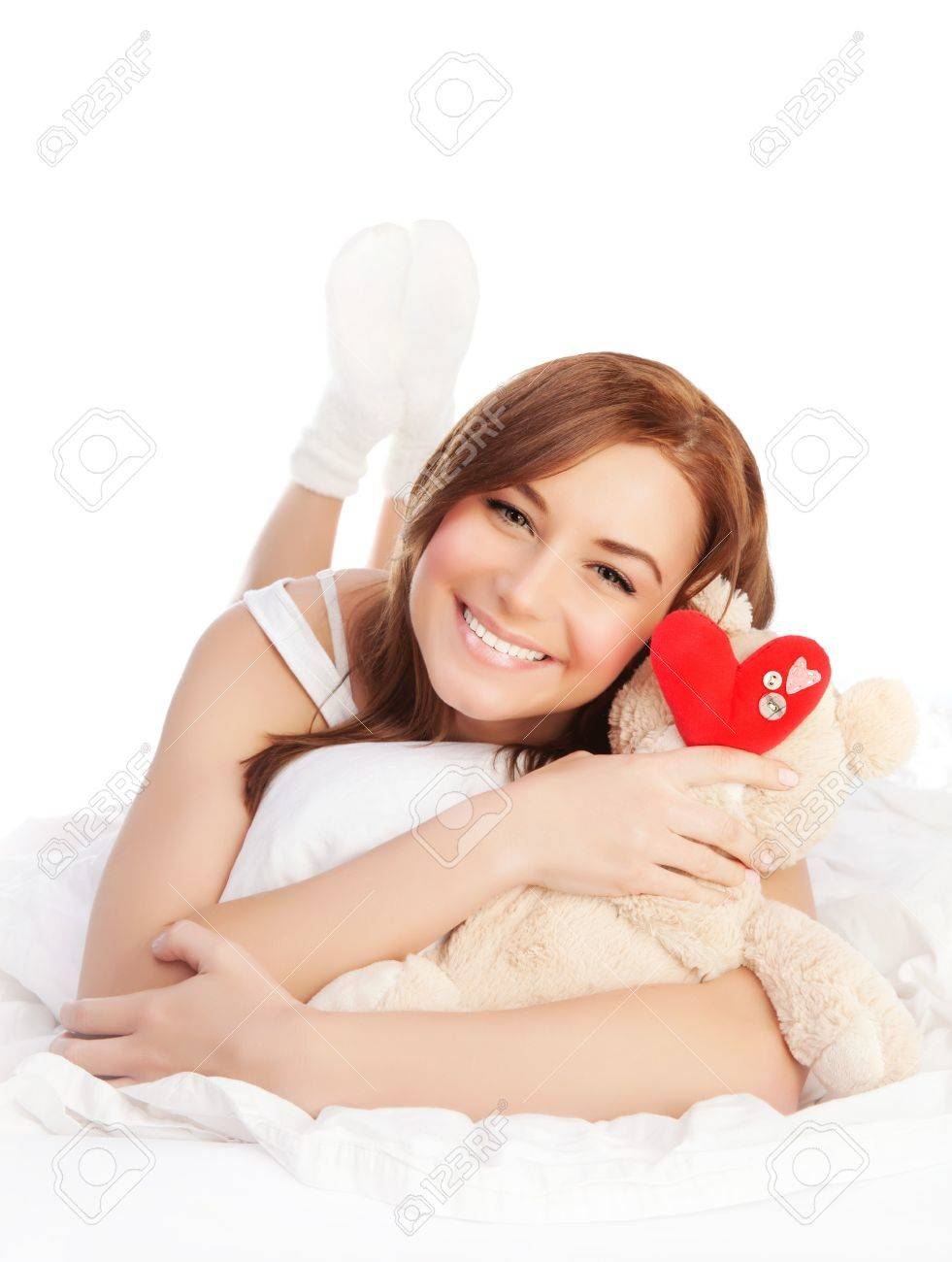 Picture of happy woman laying down in bed linen and enjoying romantic present, soft bear and red handmade heart-shape toy as gift for Valentines day holiday, isolated on white background, love concept Stock Photo - 17641381