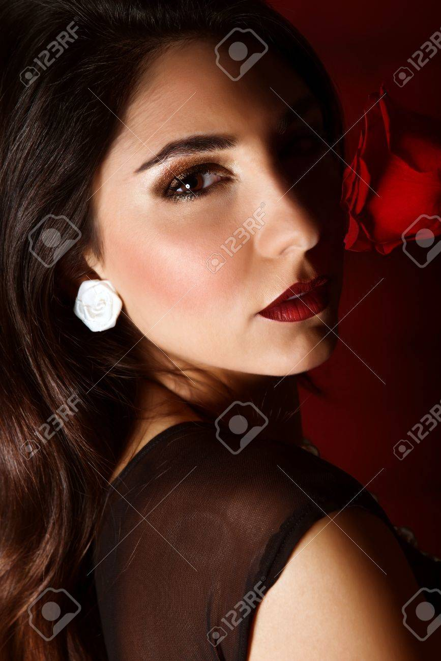 Photo of beautiful brunette woman with red rose isolated on dark background, closeup portrait of gorgeous female with perfect makeup, luxury beauty salon, Valentine day, passion and elegance concept Stock Photo - 17792518