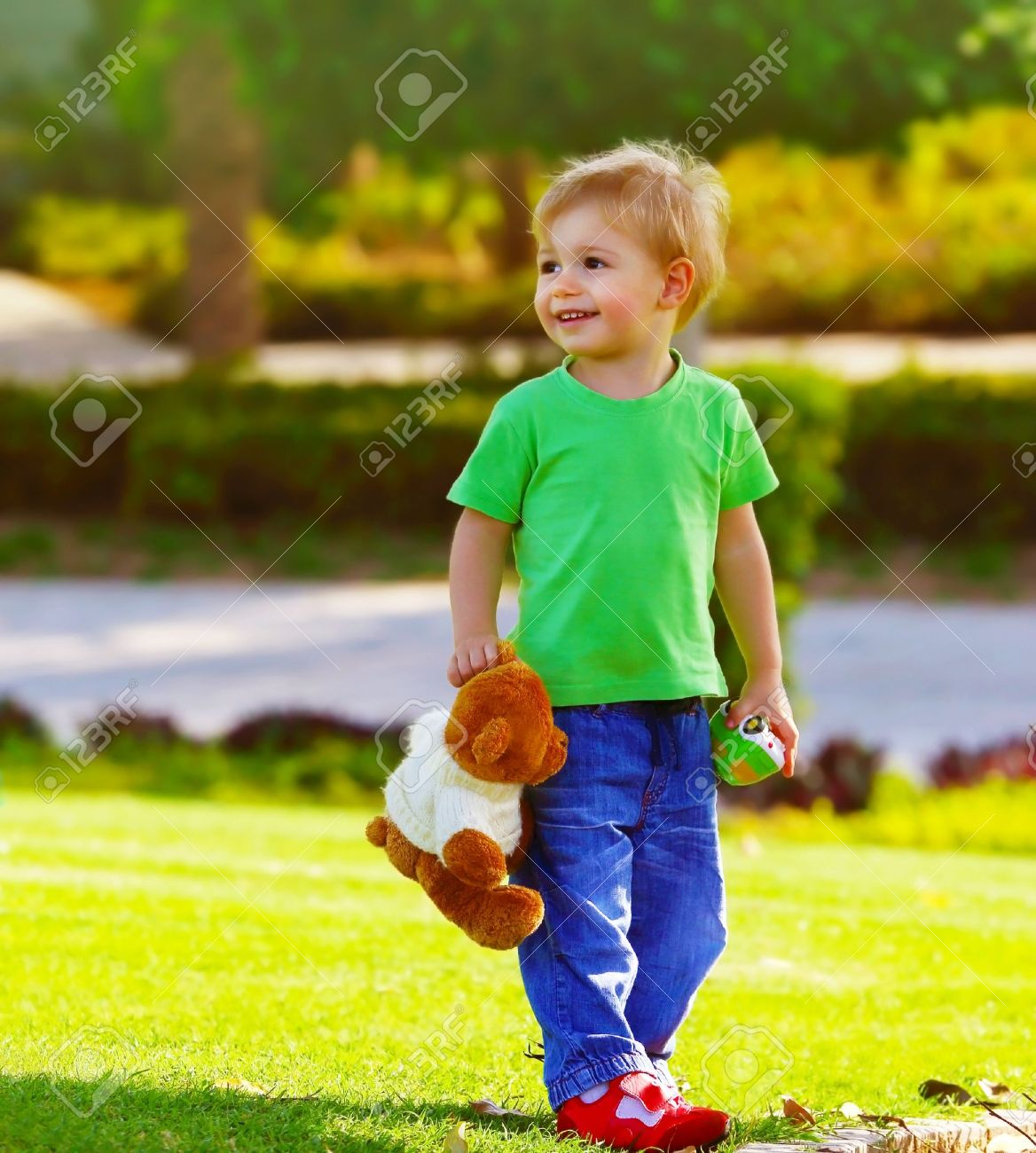 photo of cute small boy in the park holding teddy bear adorable
