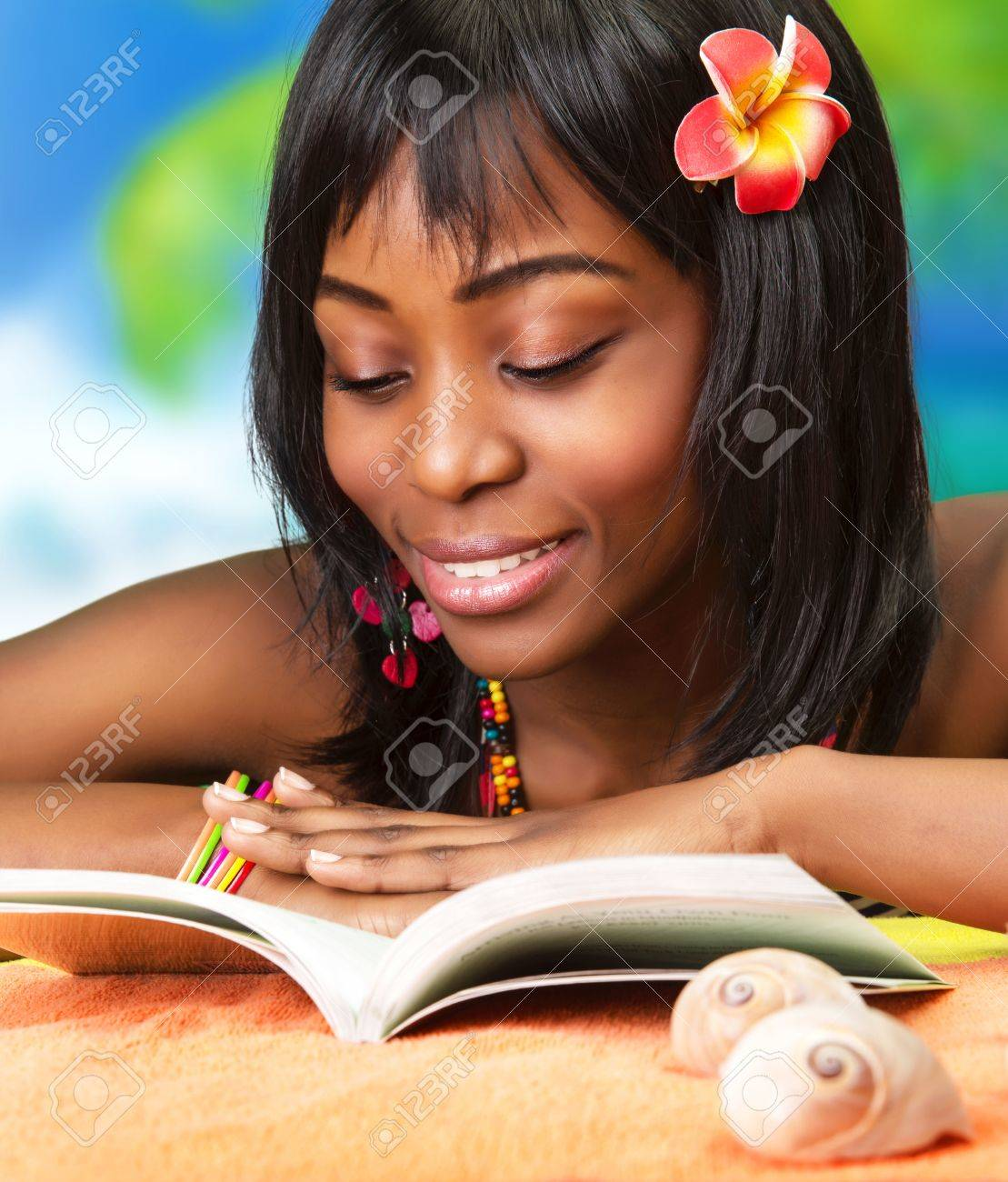 Photo of beautiful african woman read book on the beach, pretty black female enjoying summer vacation, cute young lady with red flowers in dark hair taking sunbath, happy lifestyle, luxury resort Stock Photo - 18314861