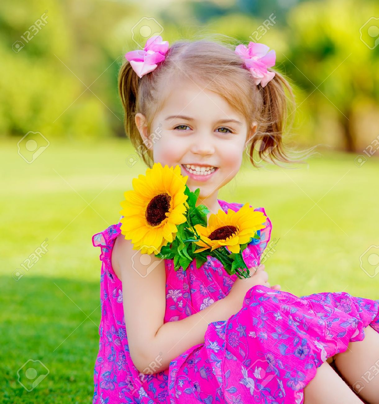 Happy baby girl playing outdoor cute child holding fresh sunflower flowers kid having fun
