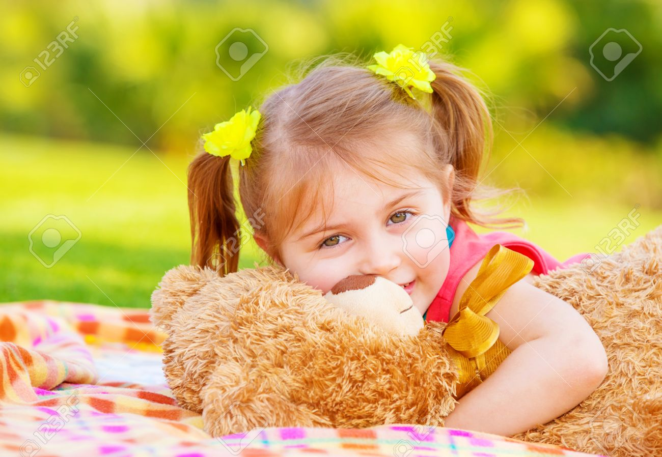 cute smiling baby girl hugging soft bear toy, sweet kid having