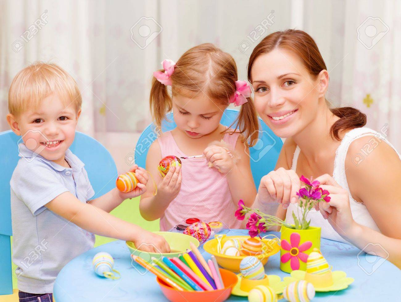 Two sweet toddler with young drawing teacher paint colorful Easter eggs, art lesson, handmade festive decor Stock Photo - 19335052