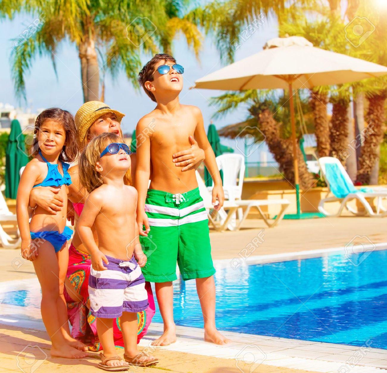 Familia feliz linda que se divierte cerca de la piscina en centro turístico tropical de lujo, la madre con los niños mirando hacia arriba en el cielo, vacaciones de verano, concepto del amor Foto de archivo - 20573939