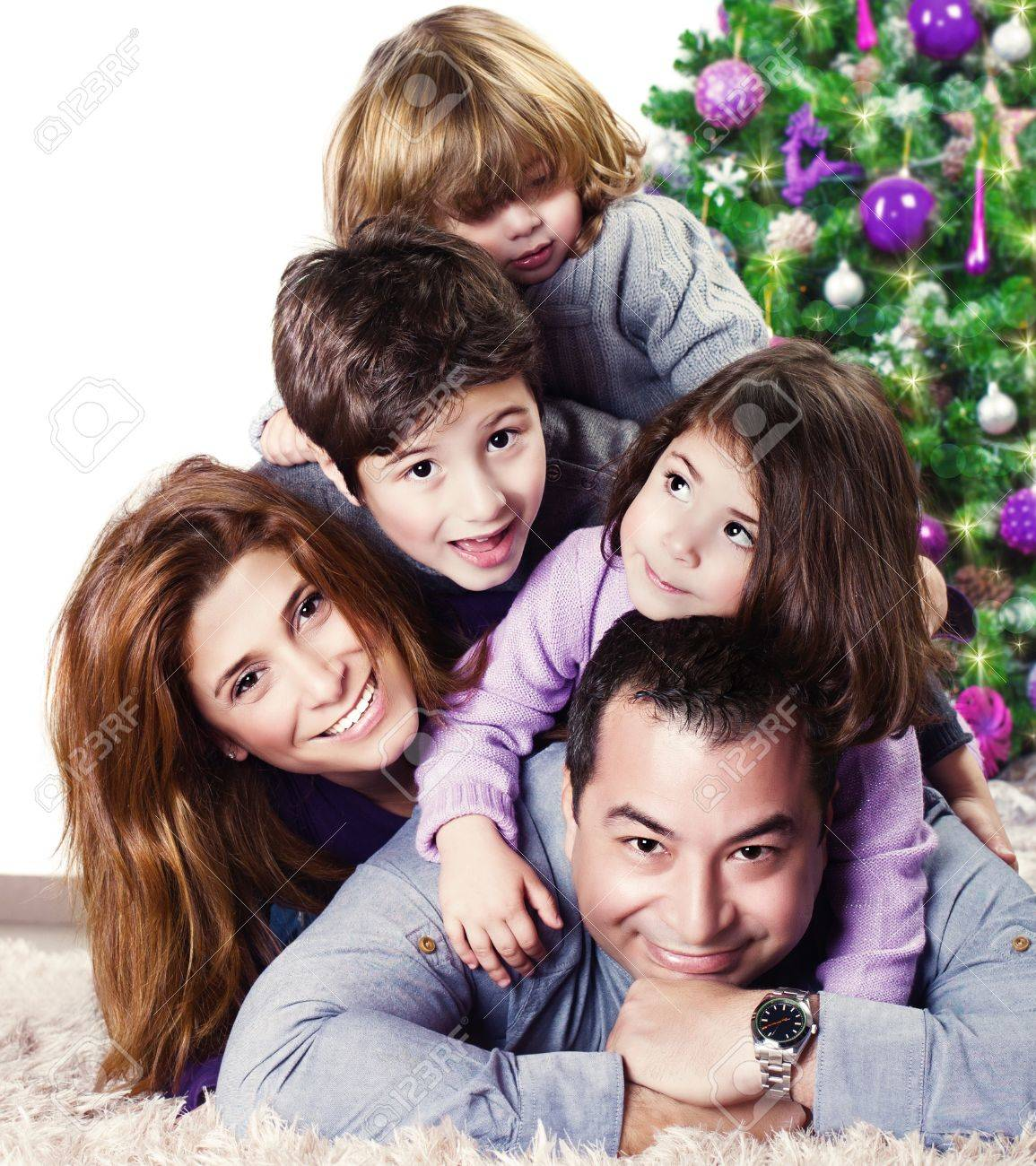 Closeup portrait of cute cheerful family lying down near Christmas tree at home, happy parents with three kids celebrate New Year holiday, love concept Stock Photo - 20573938
