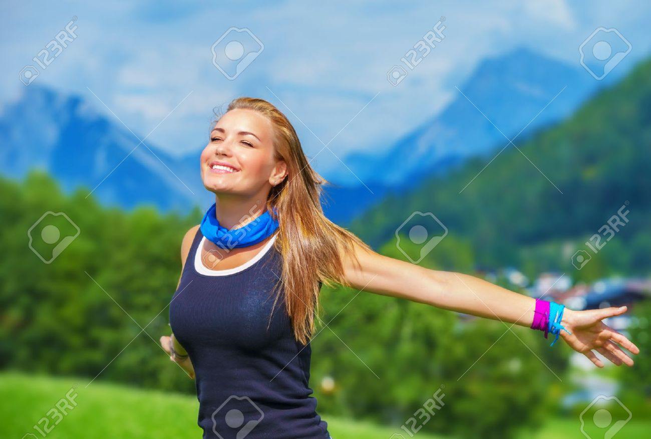 Portrait of happy traveler girl with raised up hands enjoying sunny day, mountains landscape, travel to Europe, happiness emotion, summer holiday concept Stock Photo - 21706888