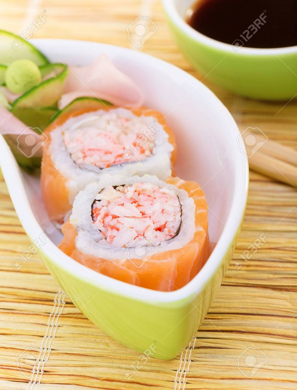 Delicious sushi served with chopsticks and soy sauce, tasty roll with crab meat and raw salmon, traditional asian food, healthy eating concept Stock Photo - 22631428