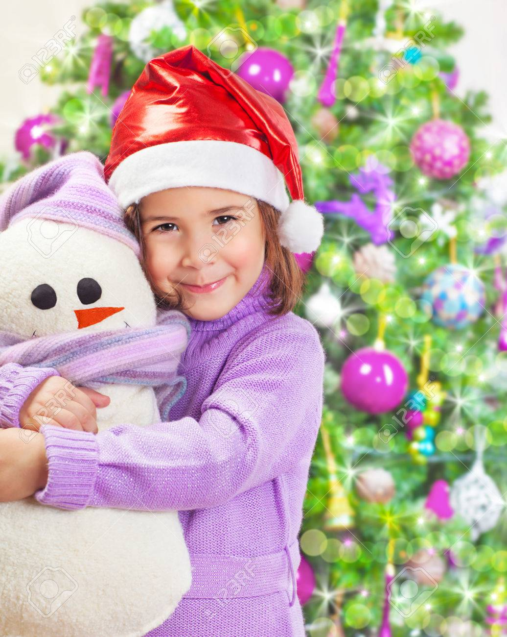 Beautiful little happy girl wearing red Santa hat and holding in hands snowman soft toy, Christmas tree, happy winter holidays Stock Photo - 23015050