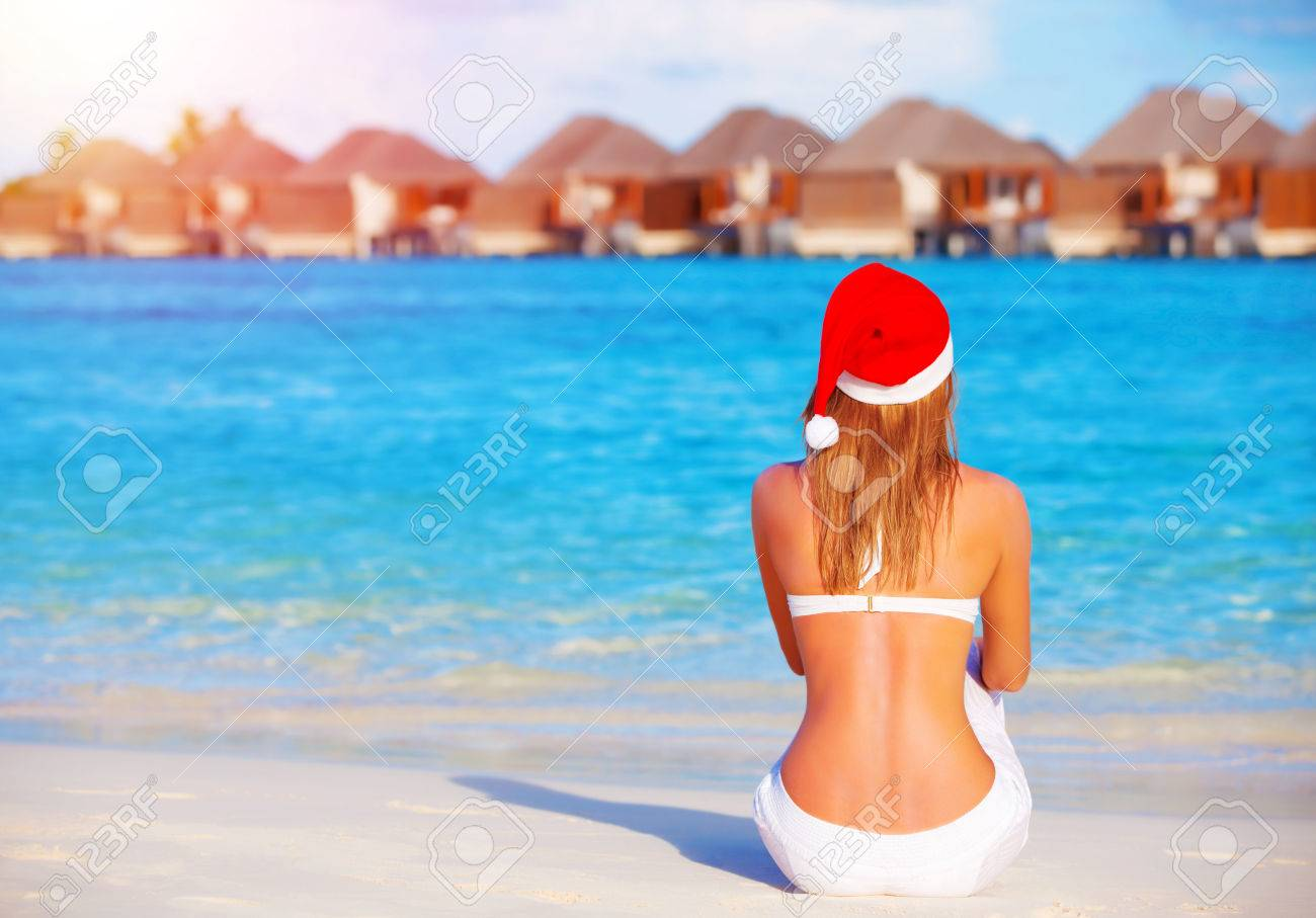 New Year celebration on Maldives, travel on winter holidays to summer destinations, back side, wearing red Santa Claus hat Stock Photo - 23569410