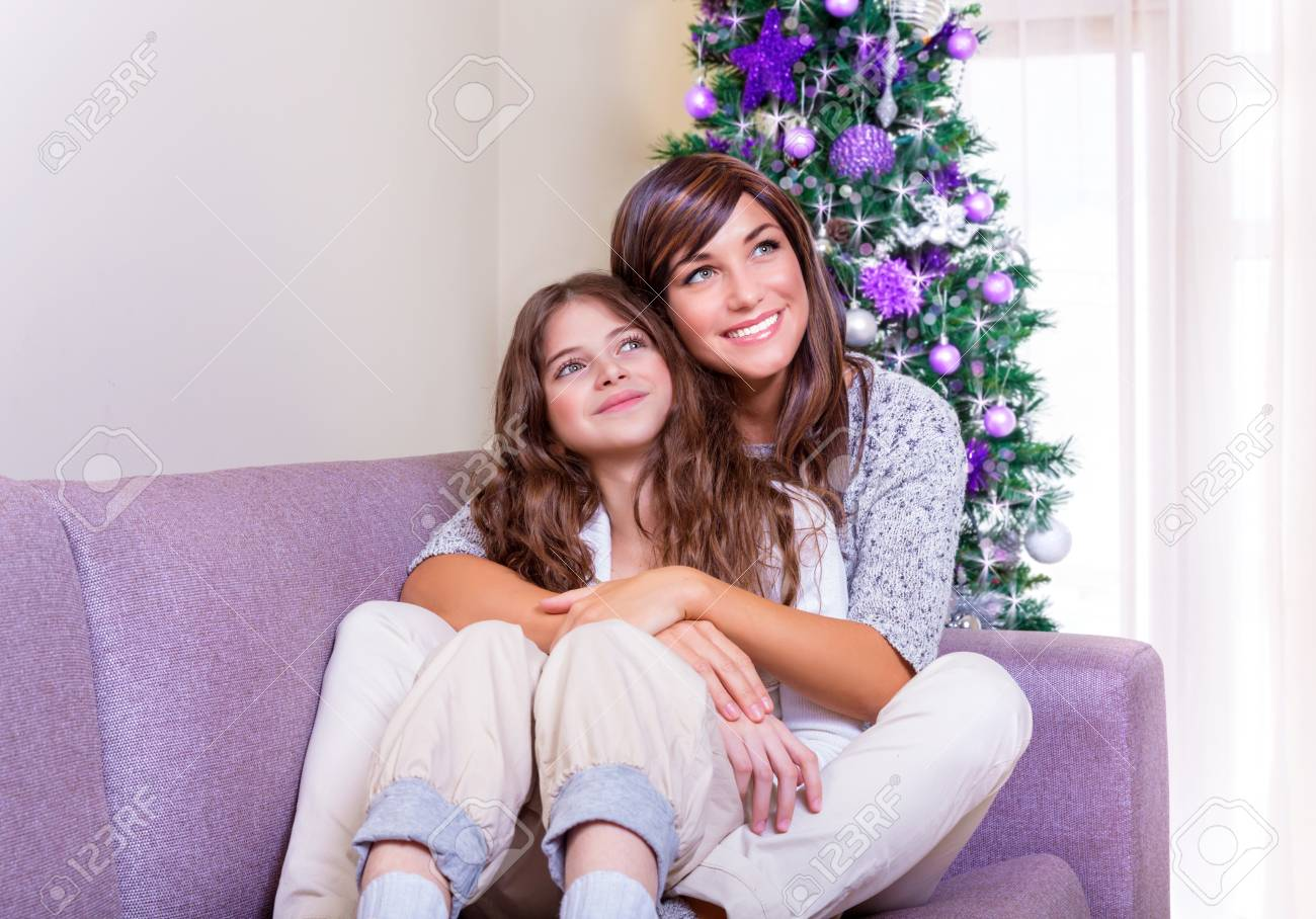 New Year celebration at home, mother sitting with daughter at home near Christmas tree and enjoying warm cozy Xmas evening Stock Photo - 23949932