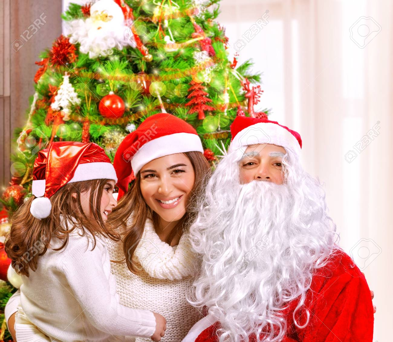 Christmas party, happy family at home celebrating New Year, mother with daughter and Santa claus near Xmas tree, happiness concept Stock Photo - 24262552