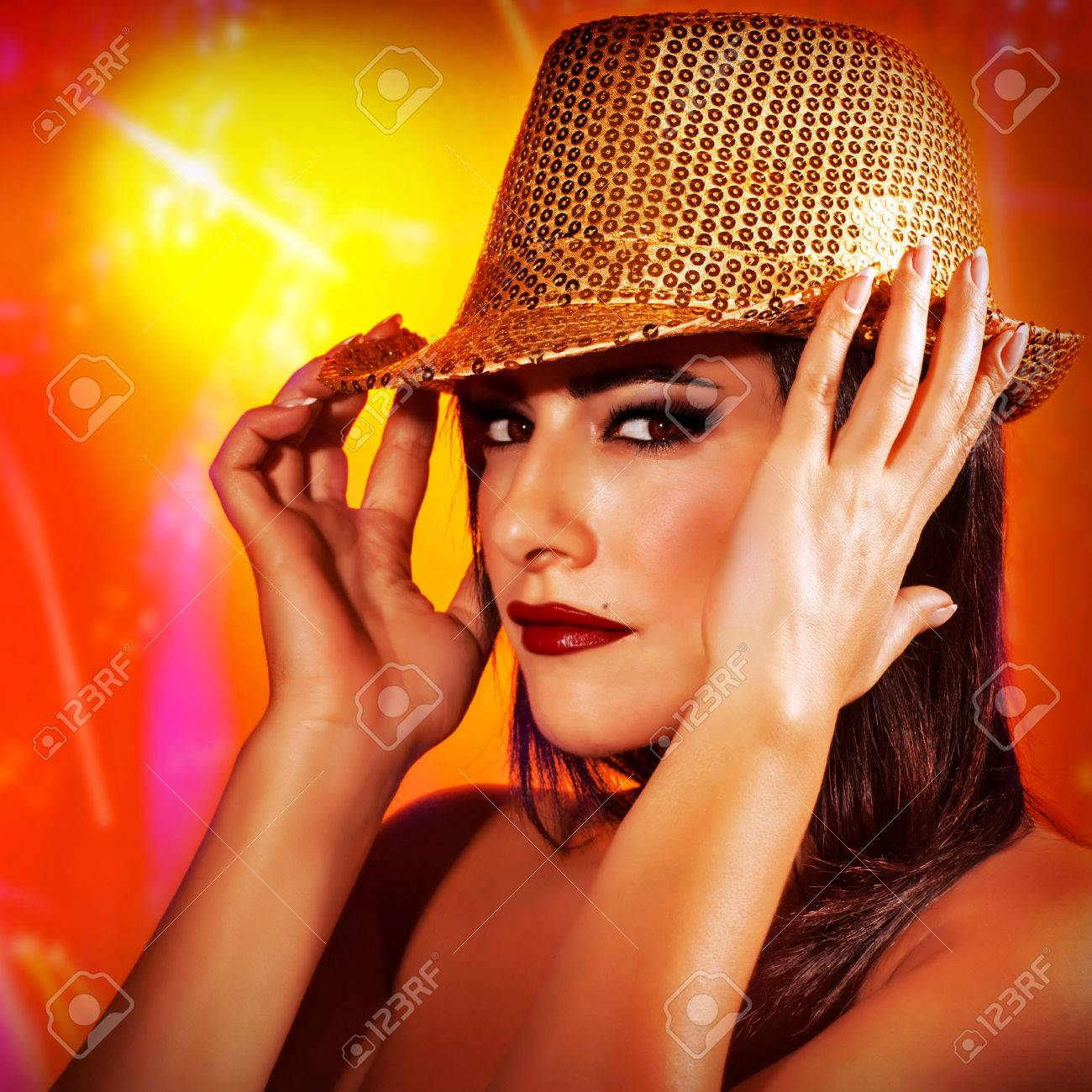 Closeup portrait of beautiful woman wearing golden shiny hat on red background, disco club, New Year celebration, fashion concept Stock Photo - 24262563