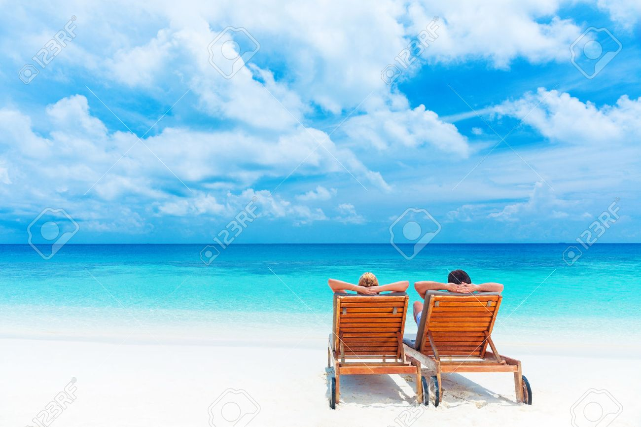 Two Happy People Relaxing On The Beach Sitting Down Comfortable Sunbed And Taking Sunbath