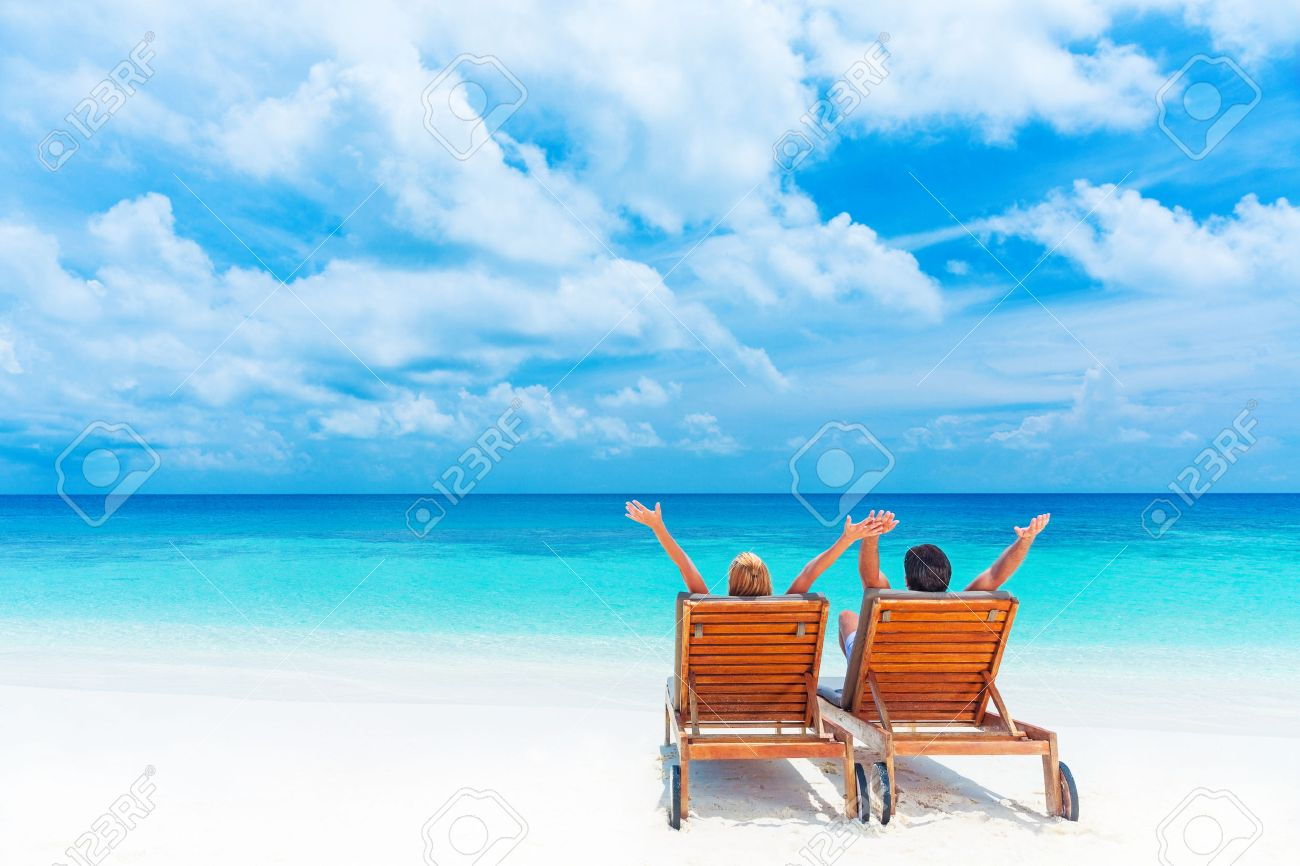 Two Happy People Relaxing On The Beach Sitting Comfortable Sunbed With Raised Up Hands