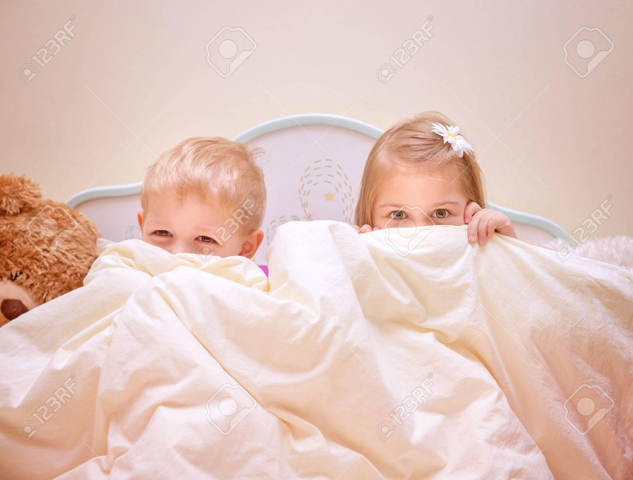 Zwei fröhliche kinder spiel spielt im schlafzimmer, geschwister ...