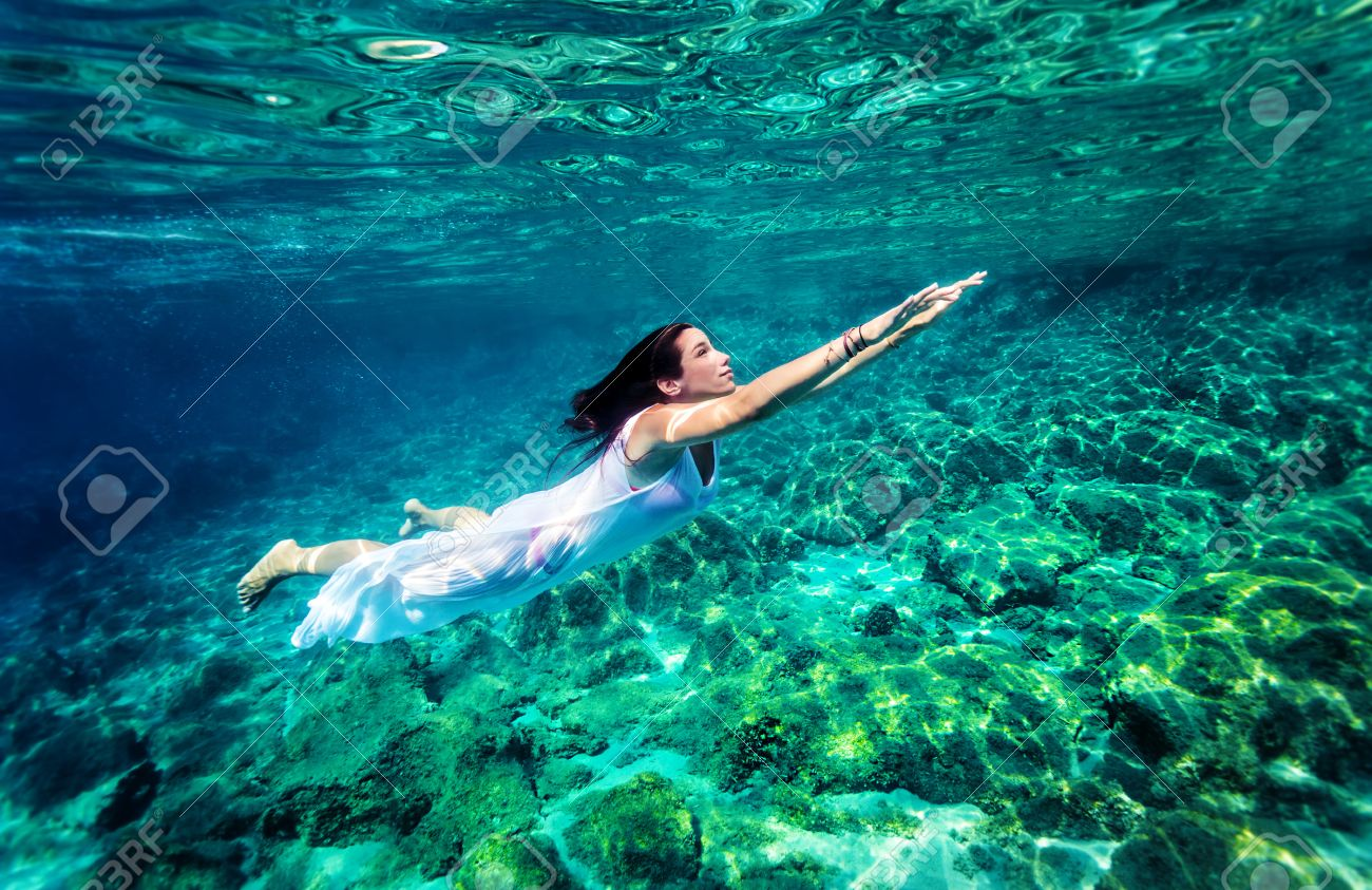 b2a801e15d Refreshing swimming underwater, beautiful young woman wearing fashion white  long dress and dive into clear