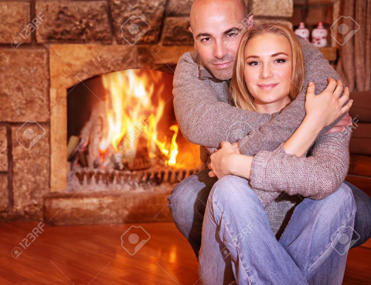 portrait of gentle couple sitting near fireplace at home romantic